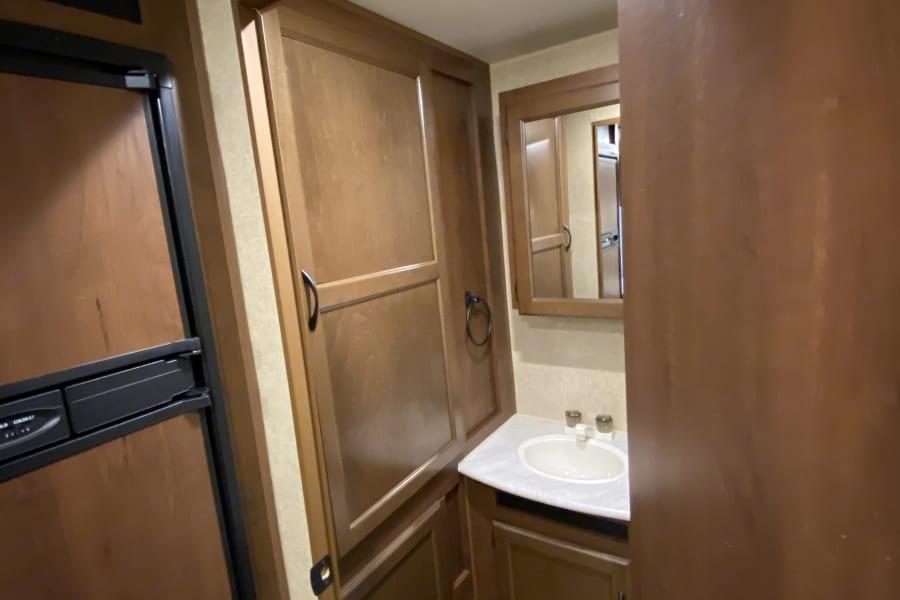 View of vanity, sink and storage.