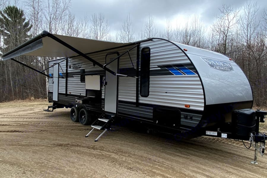 This camper has two entrances for easy access to the living area and bathroom. The awning is great for staying out of the sun.