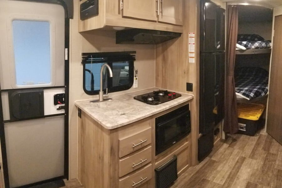 Kitchen with sink, microwave, 2 burner stove top and large fridge with freezer