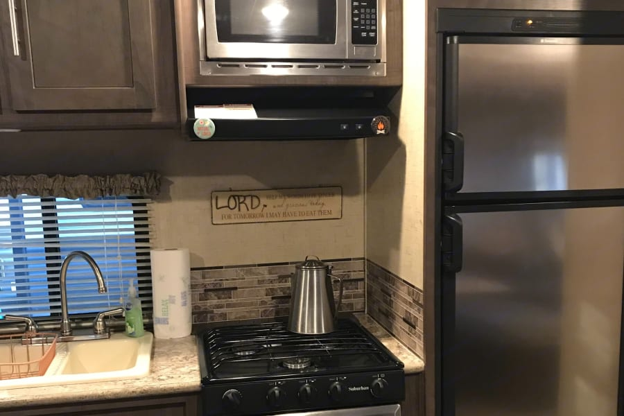Kitchen area including a gas stove/oven, electric microwave, gas/electric refrigerator.
