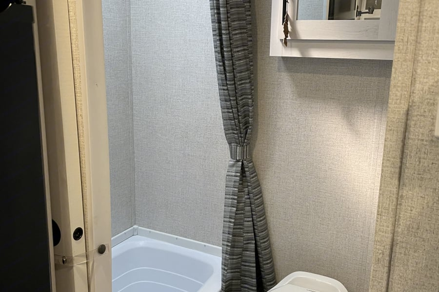 Separate shower/bath and toilet.  Sliding door for privacy.