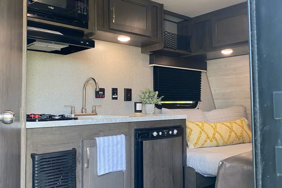 Full kitchen with refrigerator, freezer, 2-burner stove, sink with tall faucet, microwave, and countertop space for preparing meals