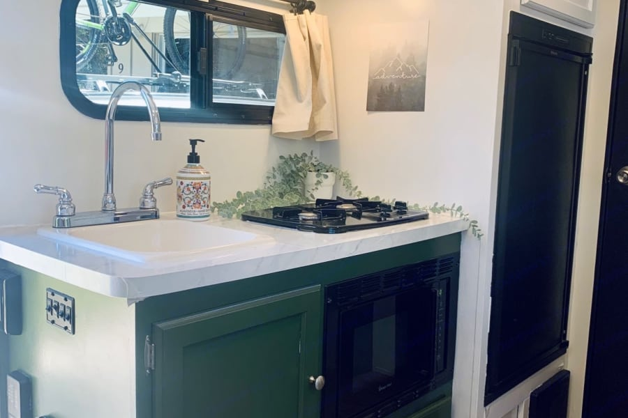 Sink, microwave, stove, fridge (with freezer compartment).