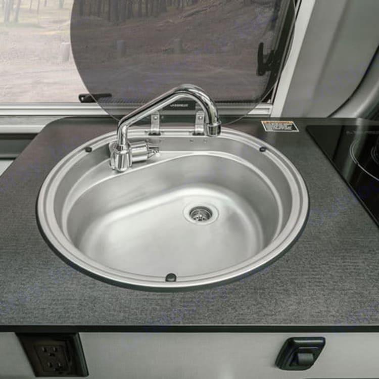 Full kitchen, including sink, stove, fridge.
