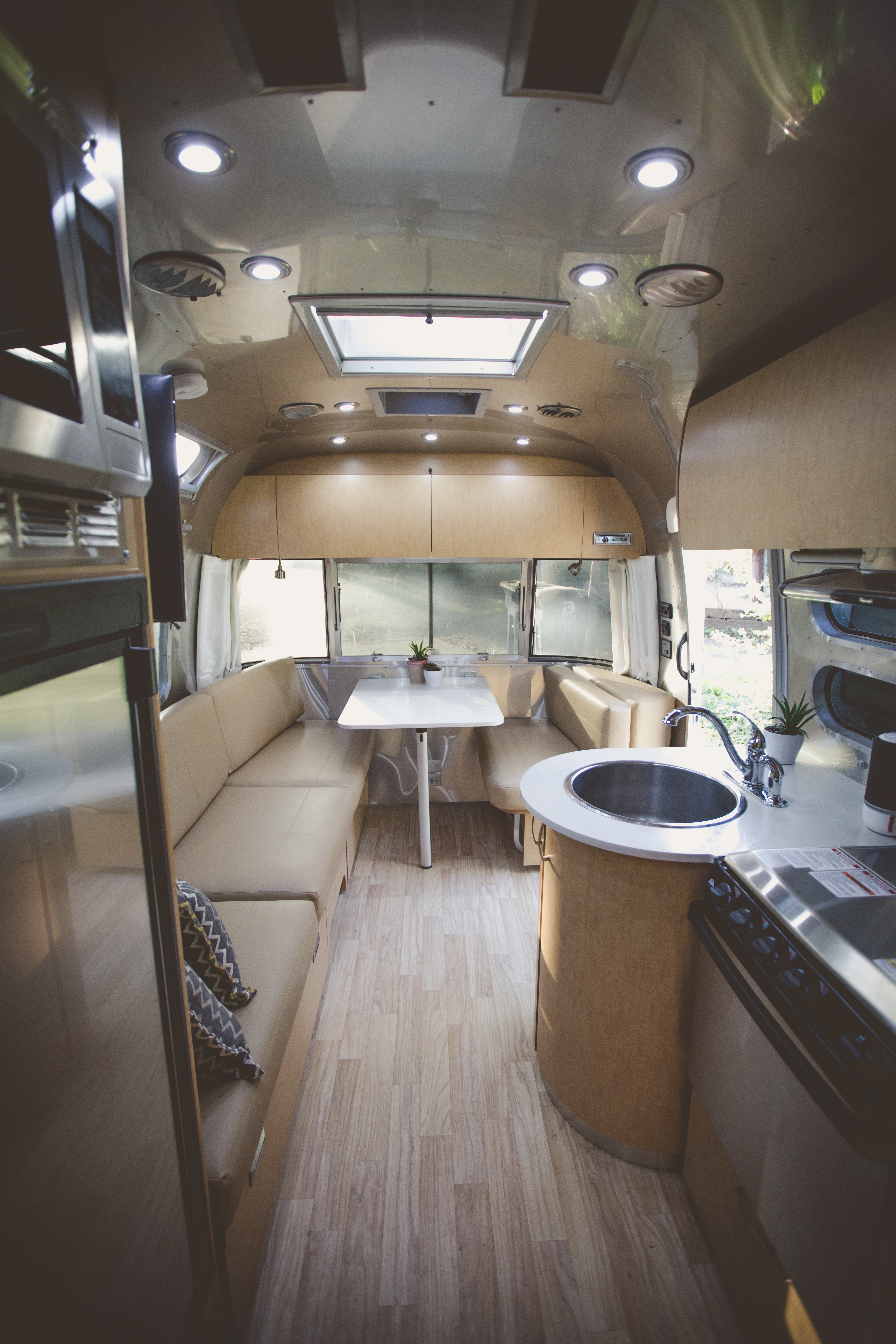 Spacious living area with dining table sofa and television.  . Airstream Flying Cloud 2017
