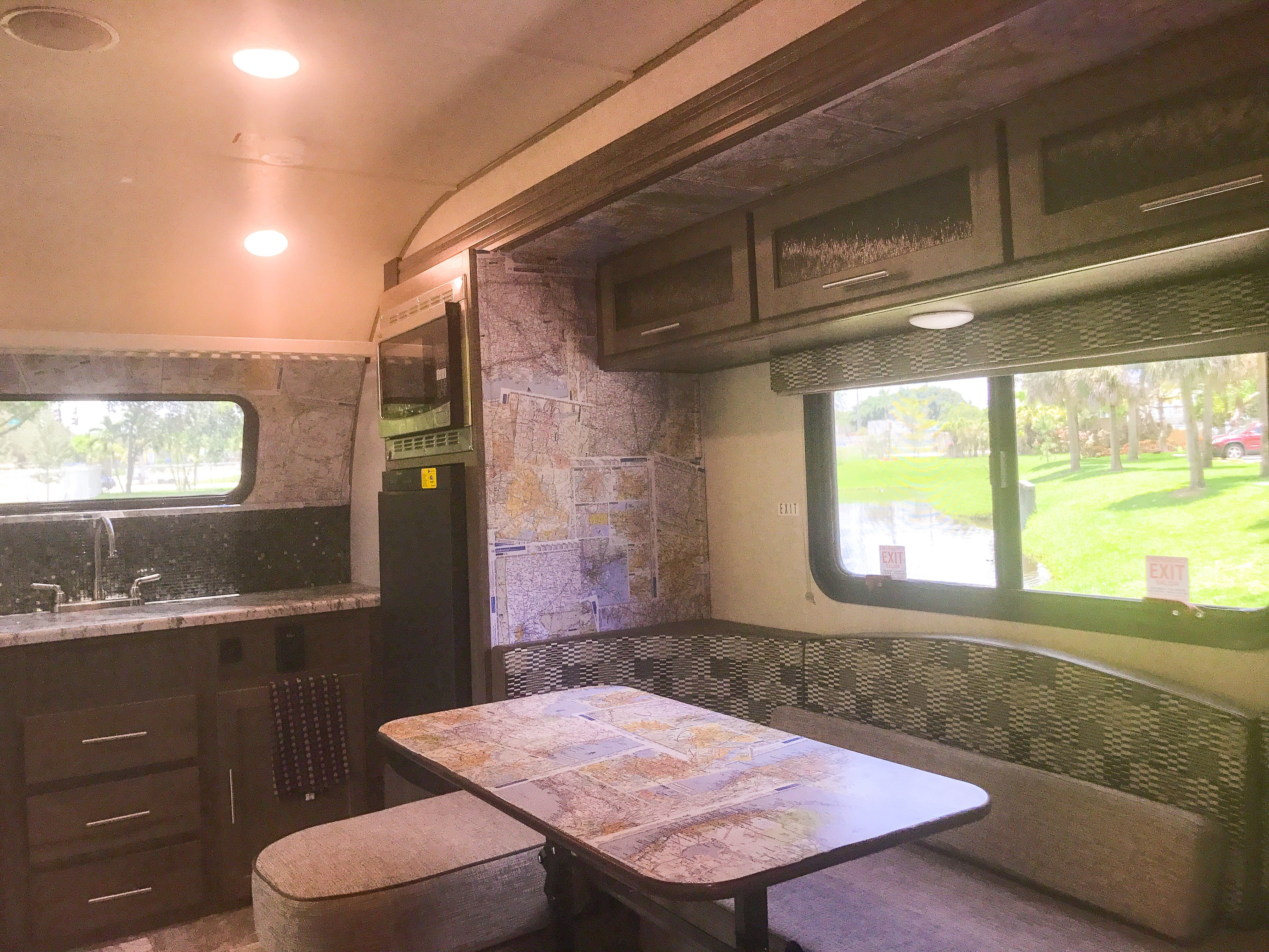 Now THAT'S a kitchen you can cook up a great camp meal in!  Fully stocked with slow cooker, blender, convection oven, microwave, keurig, pots and pans, everything you need!  Upgraded tile kitchen backsplash and decoupage map wallpaper by yours truly! -Actual travel trailer setup!