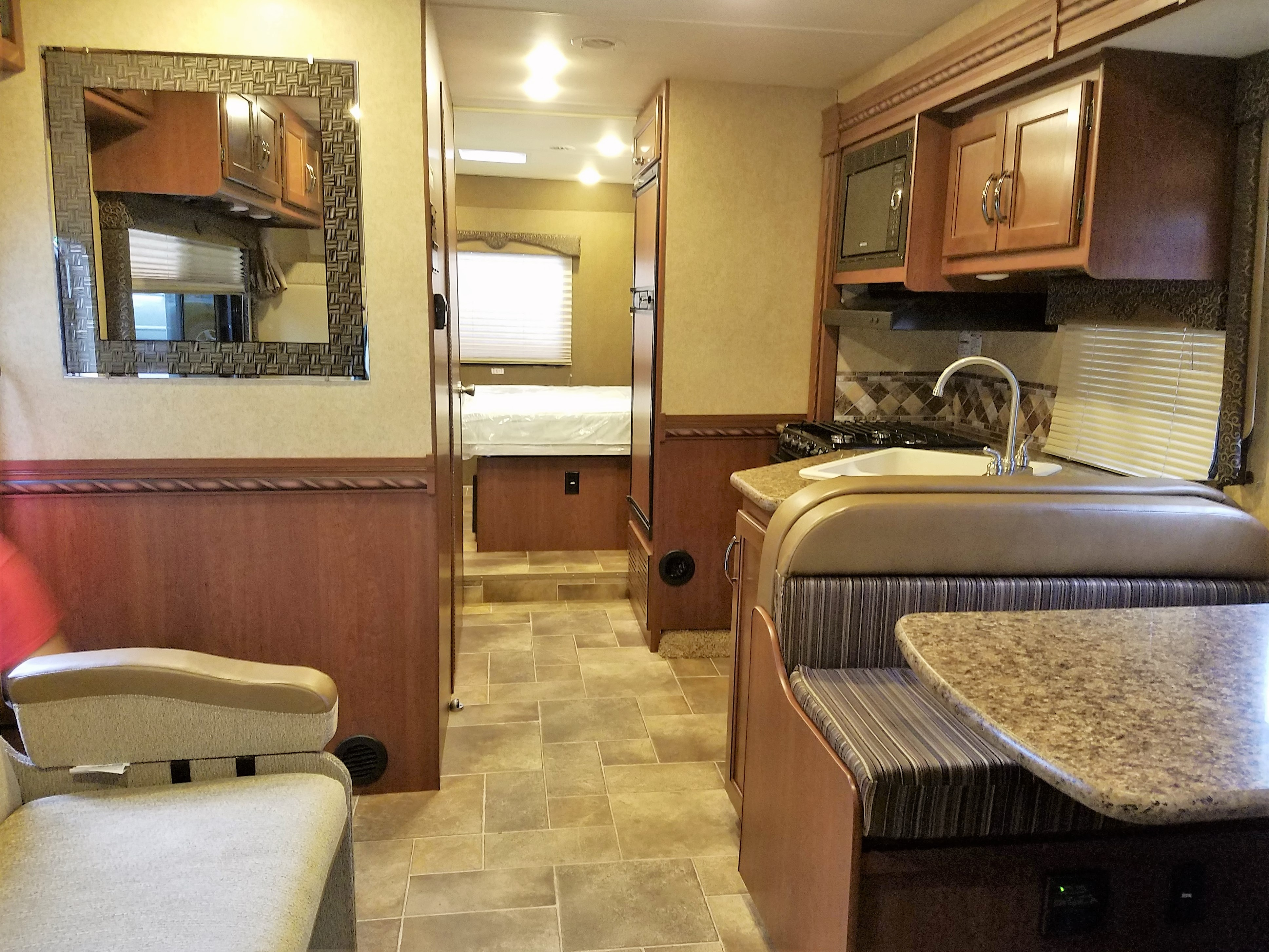 Interior of RV, looking towards the bedroom, with kitchen slide out extended. Very spacious, lots of seating.. Thor Motor Coach Freedom Elite 2016