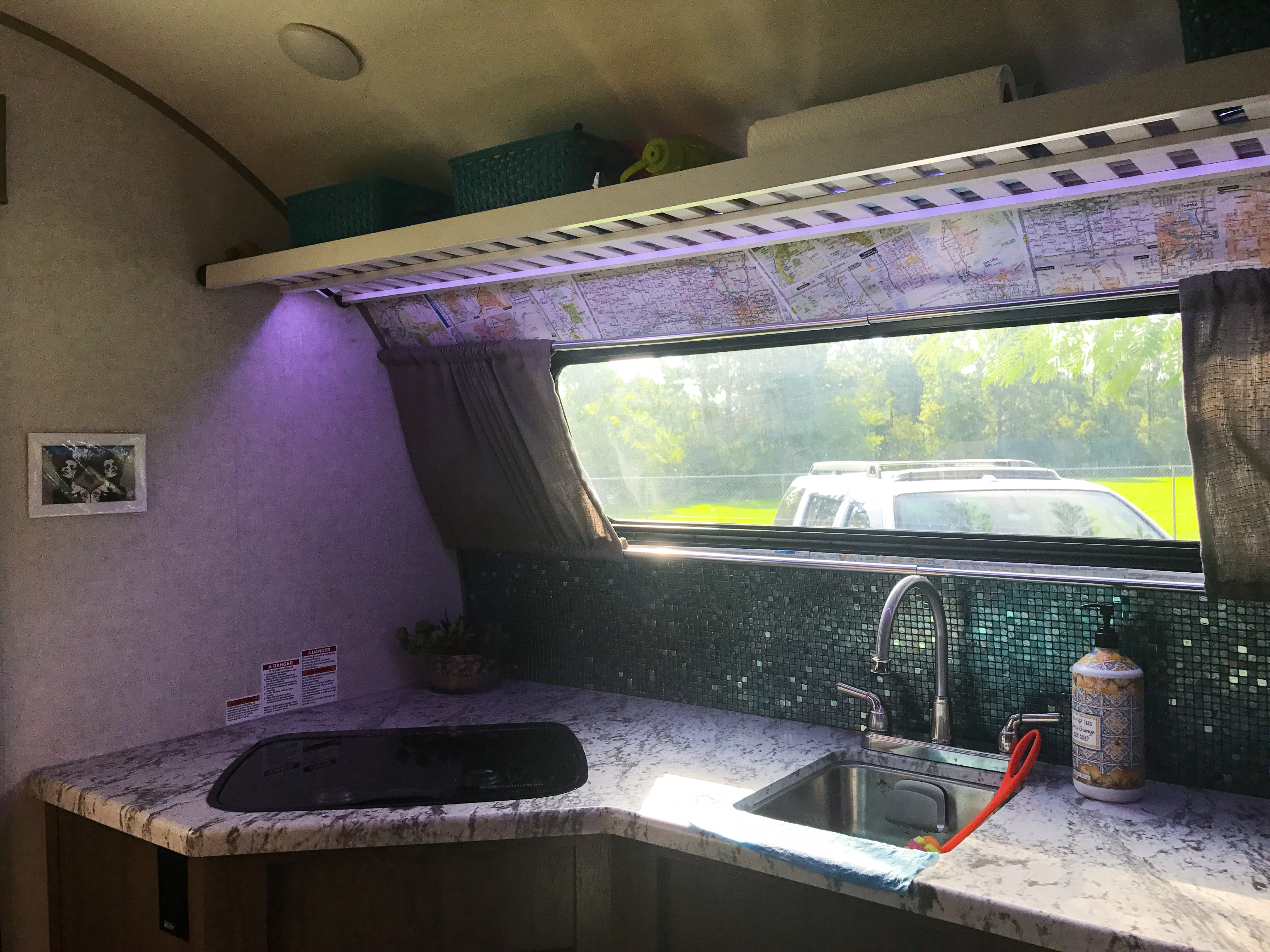 Remote controlled LED lights in the spacious kitchen. Upgraded tile kitchen backsplash and decoupage map wallpaper by yours truly! -Actual travel trailer setup!
