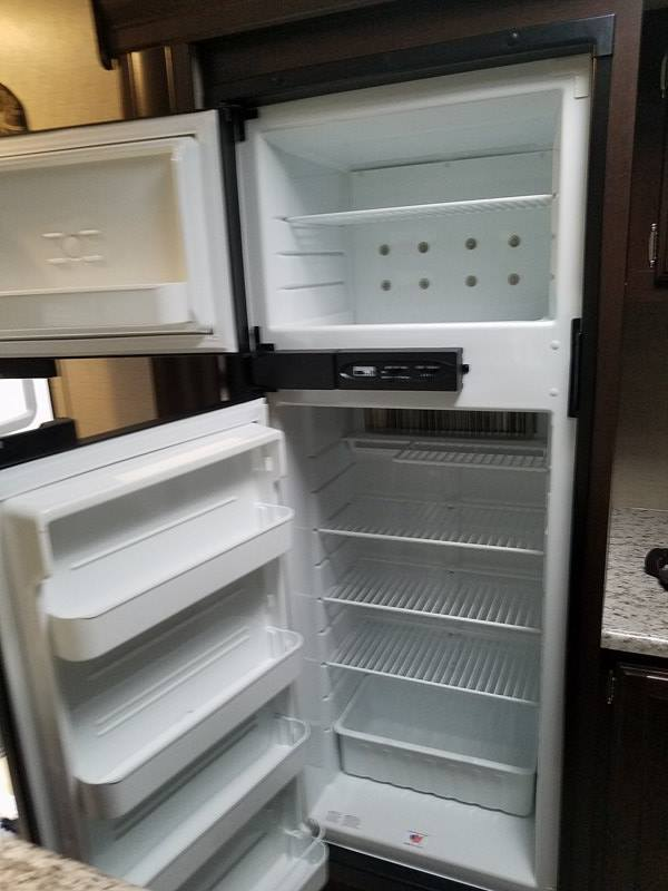 Large fridgerator runs on electricity or propane and has an auto feature in case you disconnect electricity and forget to turn on propane.. K-Z Manufacturing Sportsmen 2018