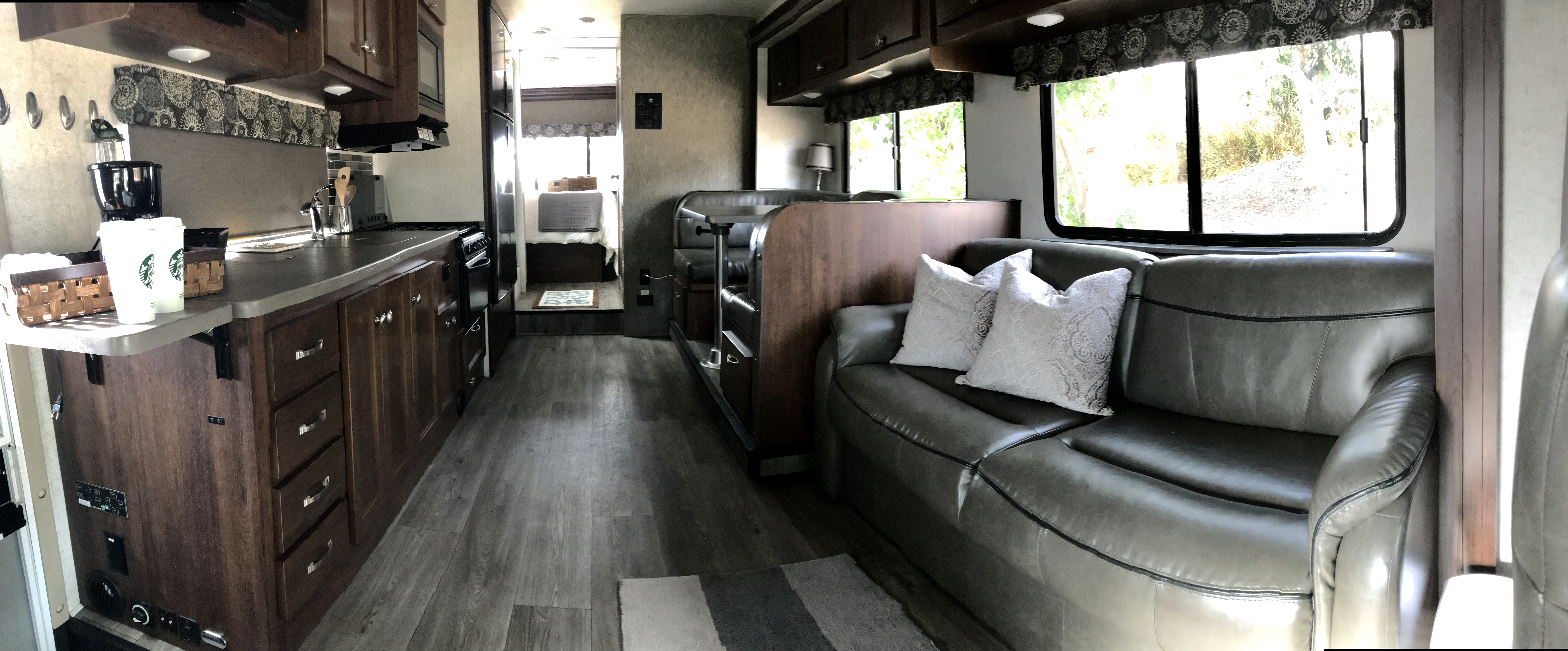 Our 2018, very modern home on wheels still smells new! Look how much light there is all the way to the back in the bedroom.  The master bed is fluffy with wonderful linens. We have lots of included extras.. Forest River Sunseeker 2018