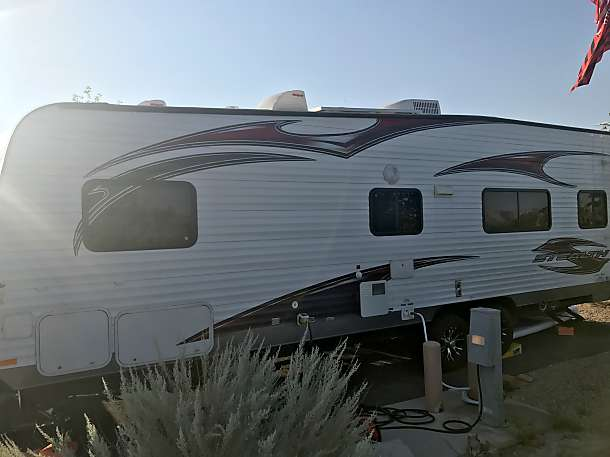Driver side, includes outdoor shower and 40 gallon gas tank.. Forest River Stealth AK2612 2014