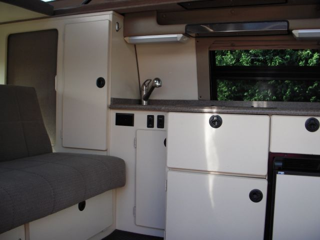 Side view of interior of van. Shows kitchen and storage.