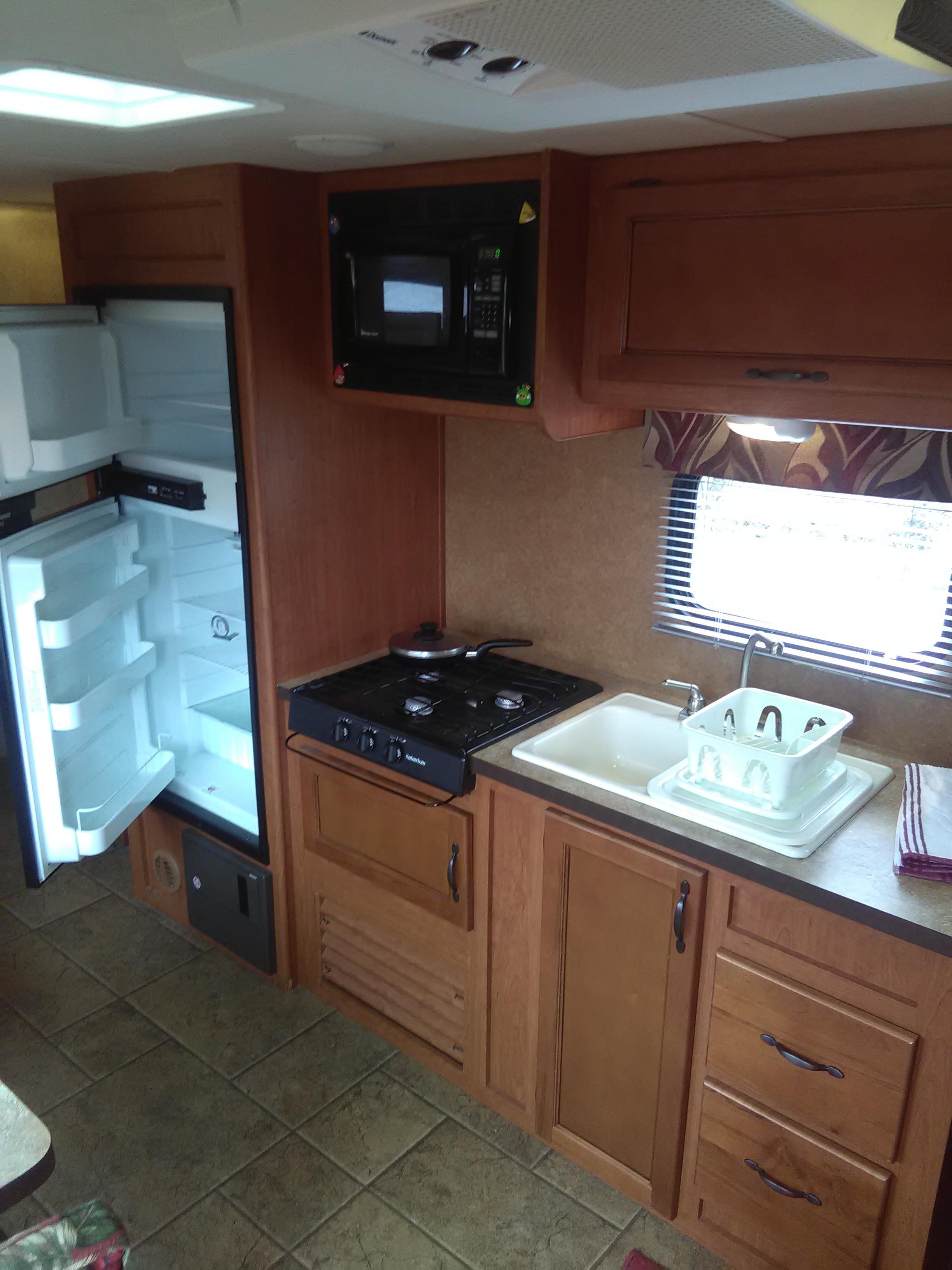 Dual sink, three burner propane stove, microwave, refrigerator/freezer works on propane, or 110VAC hookup.. Forest River Cherokee 2011