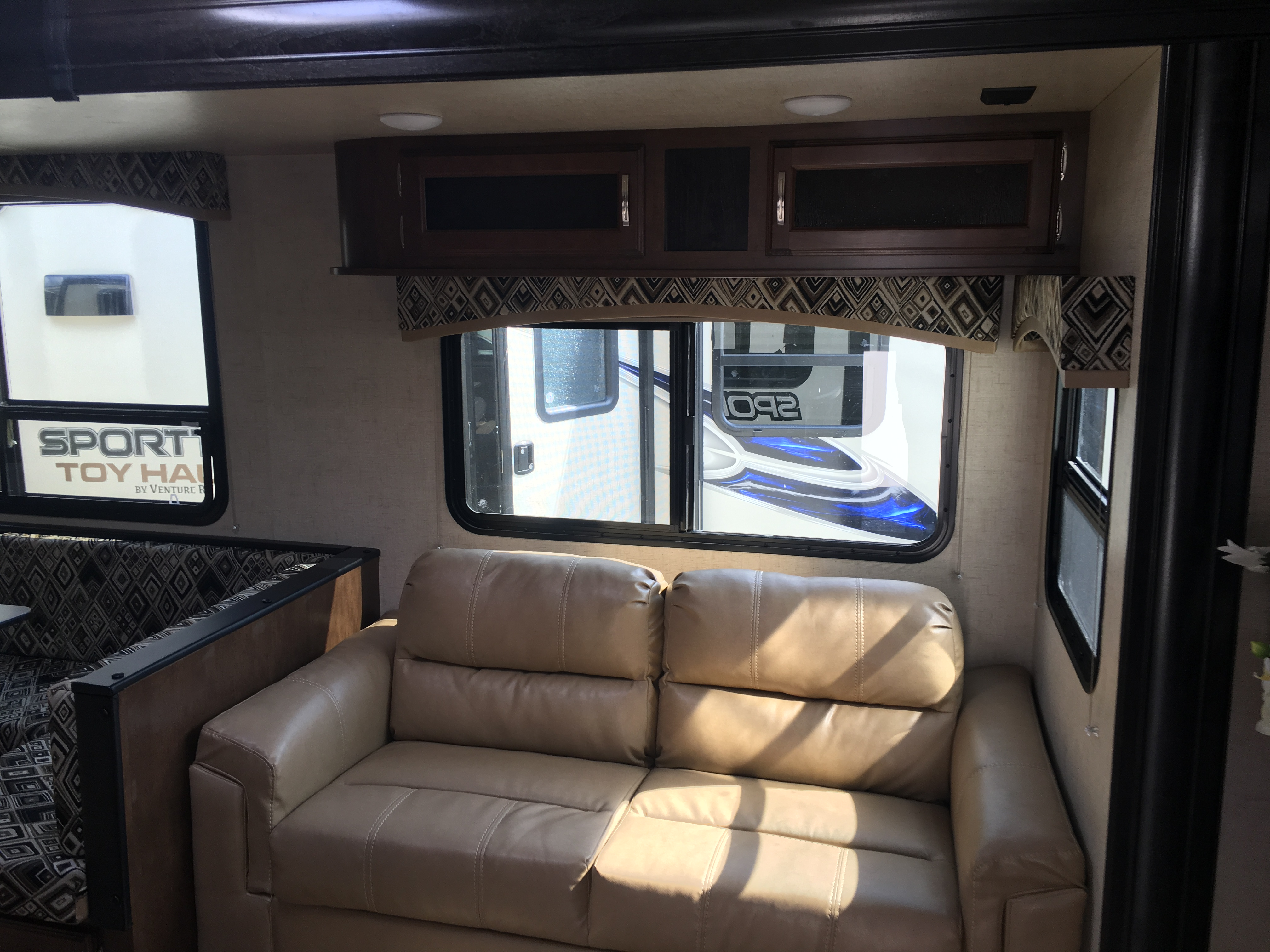 living room area, converts to single bed. Venture Rv Sporttrek 2018