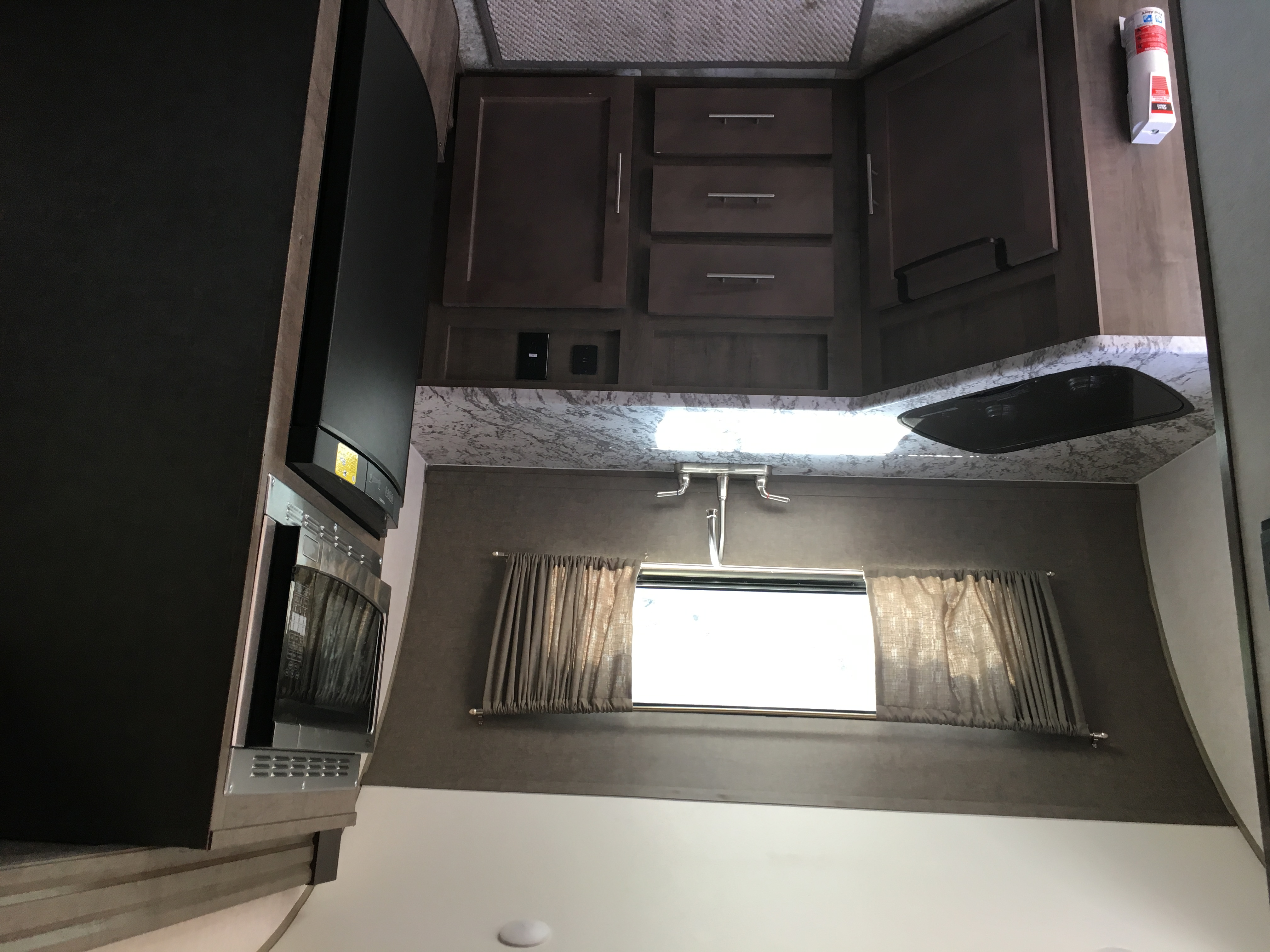 Kitchen has two burner cooktop, faucet, sink, fridge, and sink.  There are some basic pot/pan, cutlery, and plates/glasses.