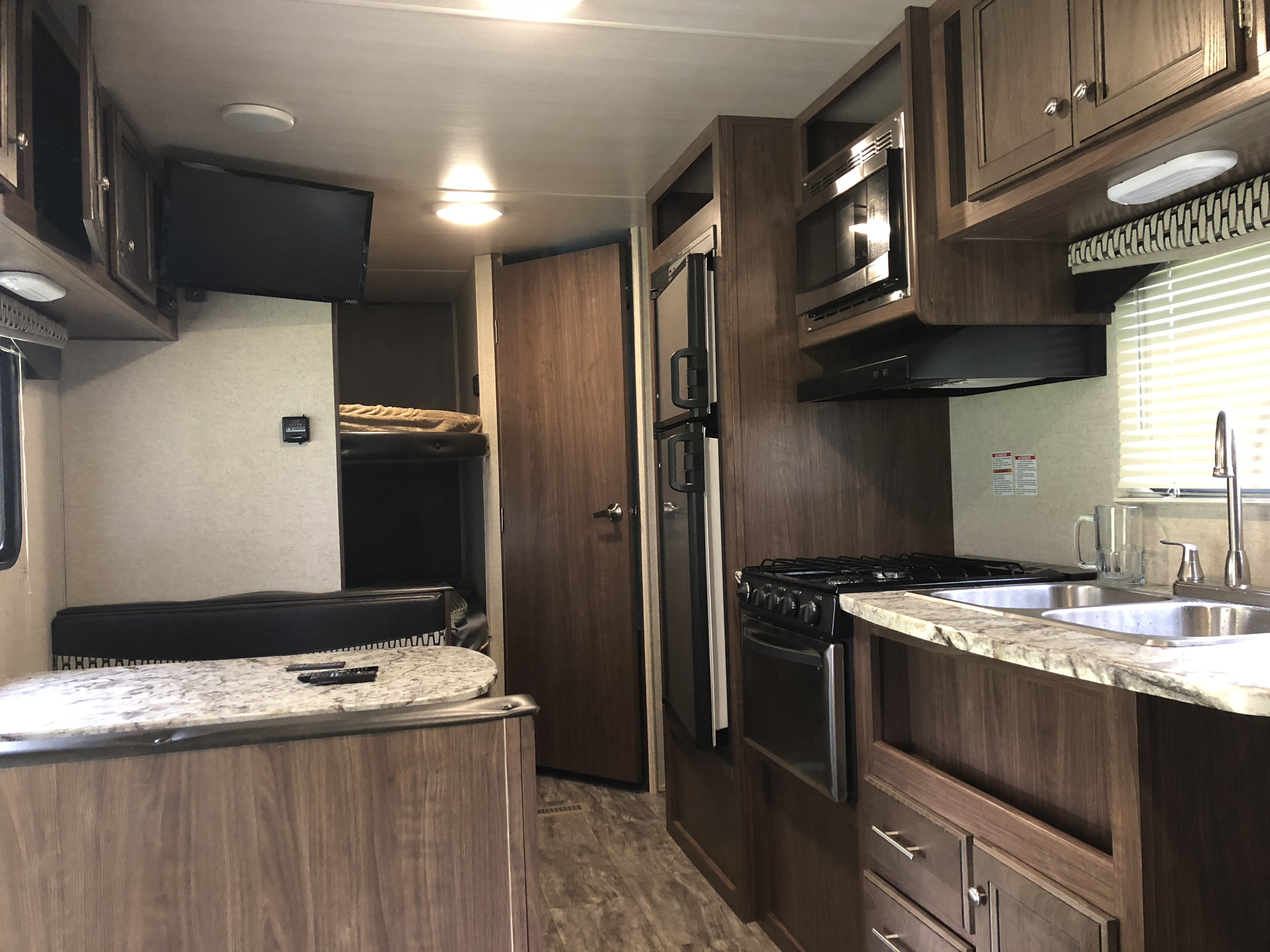 Great interior with stainless dual sinks, pantry, separate freezer and fridge, microwave, oven, 3 burner stove top and 24 inch TV Blue-ray player for entertainment. Unit also is stocked with toaster, Keurig, bluetooth radio/cd player pots pans dishes and silverware. . Heartland Trail Runner 2017