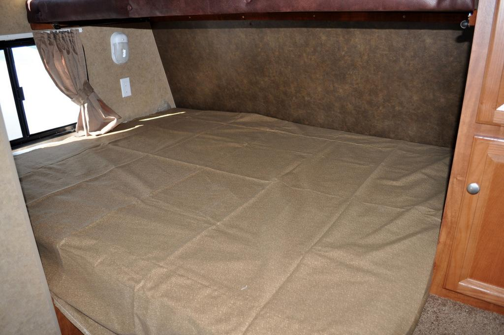 Queen bed with light, outlet, privacy curtain, cabinets, and window.. Jayco Flight 2013