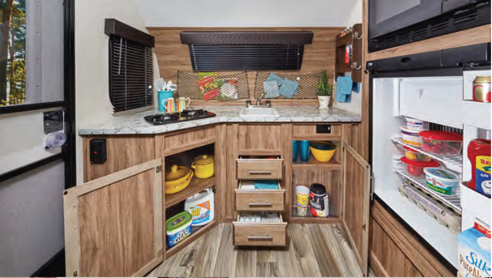 Kitchen with refrigerator, convection/microwave oven, sink, two-burner stove, and storage.. Jayco Baja 2017