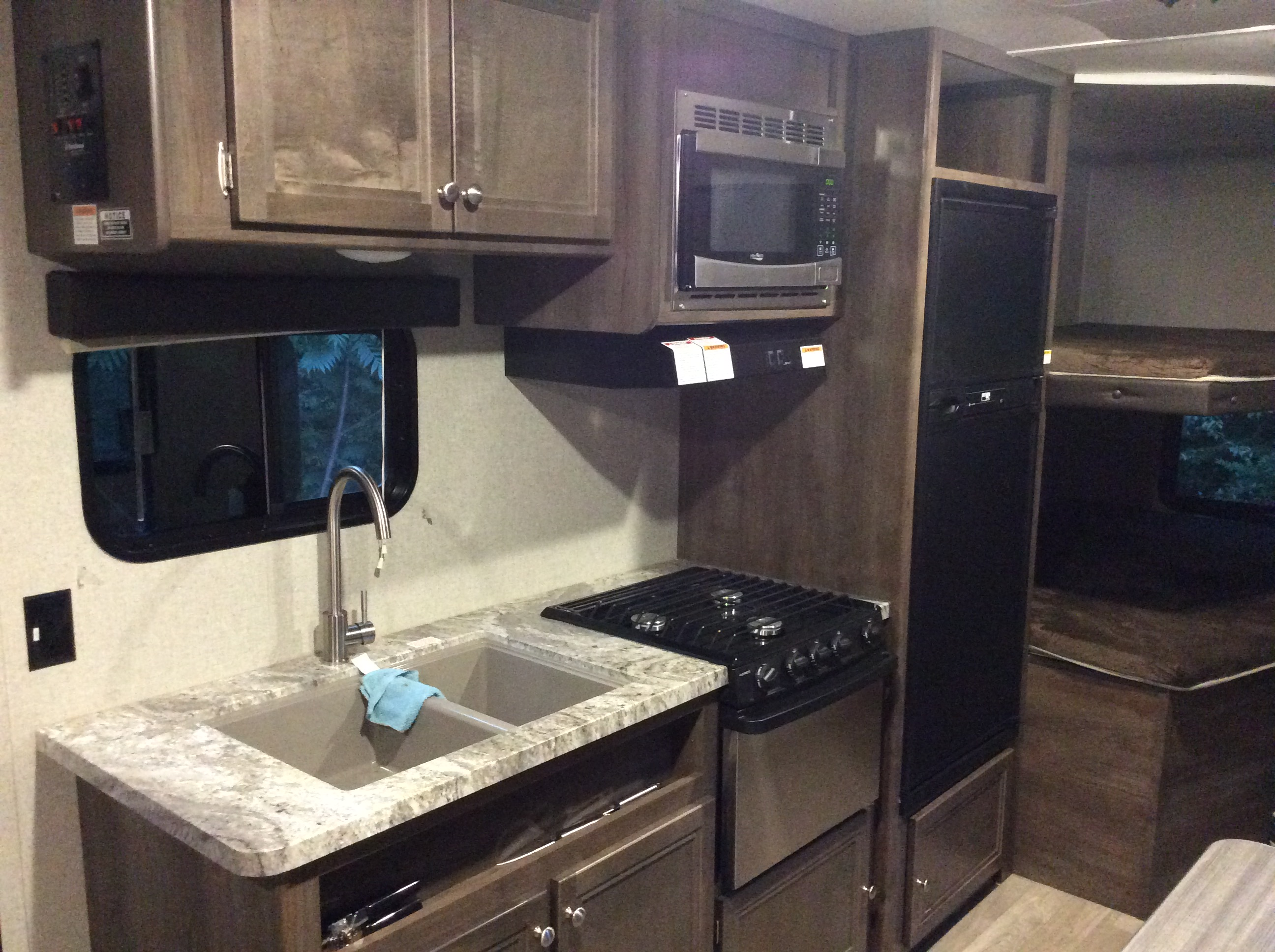 Kitchen with double sink, 3-burner stove, oven, microwave,  refrigerator and freezer.. Coleman Lantern 2018