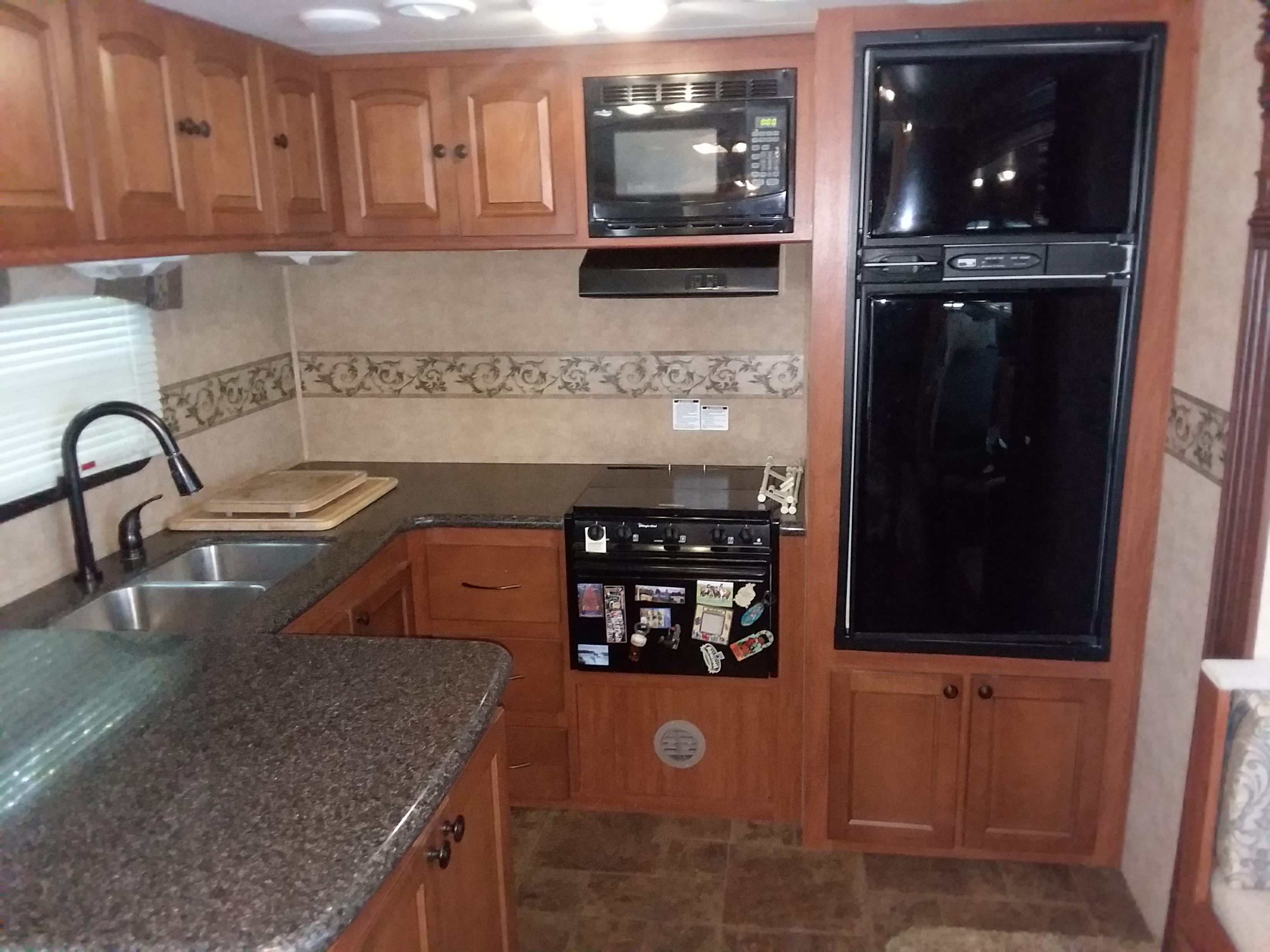 Kitchen- double stainless steel sink, microwave, refrigerator top freezer, gas stove and top and bottom cabinets.