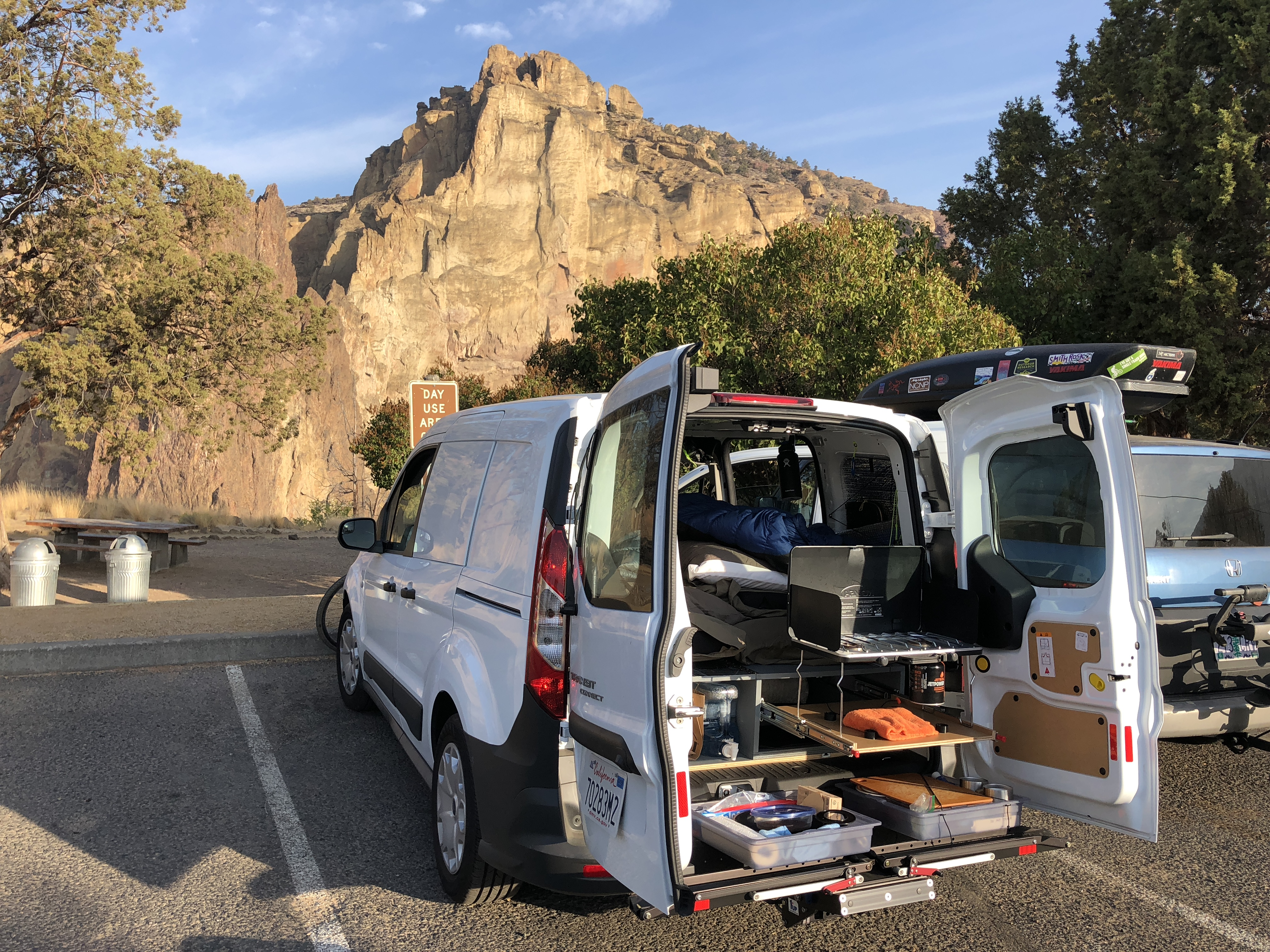 Photo no longer representative. Modified pictured setup for more storage under sleeping platform and easier, more-open access. No longer includes slider platform for stove but does include mobile kitchen, which is easy to setup outside the van or on a campground picnic table. See next images.. Ford Transit Connect SWB 2018