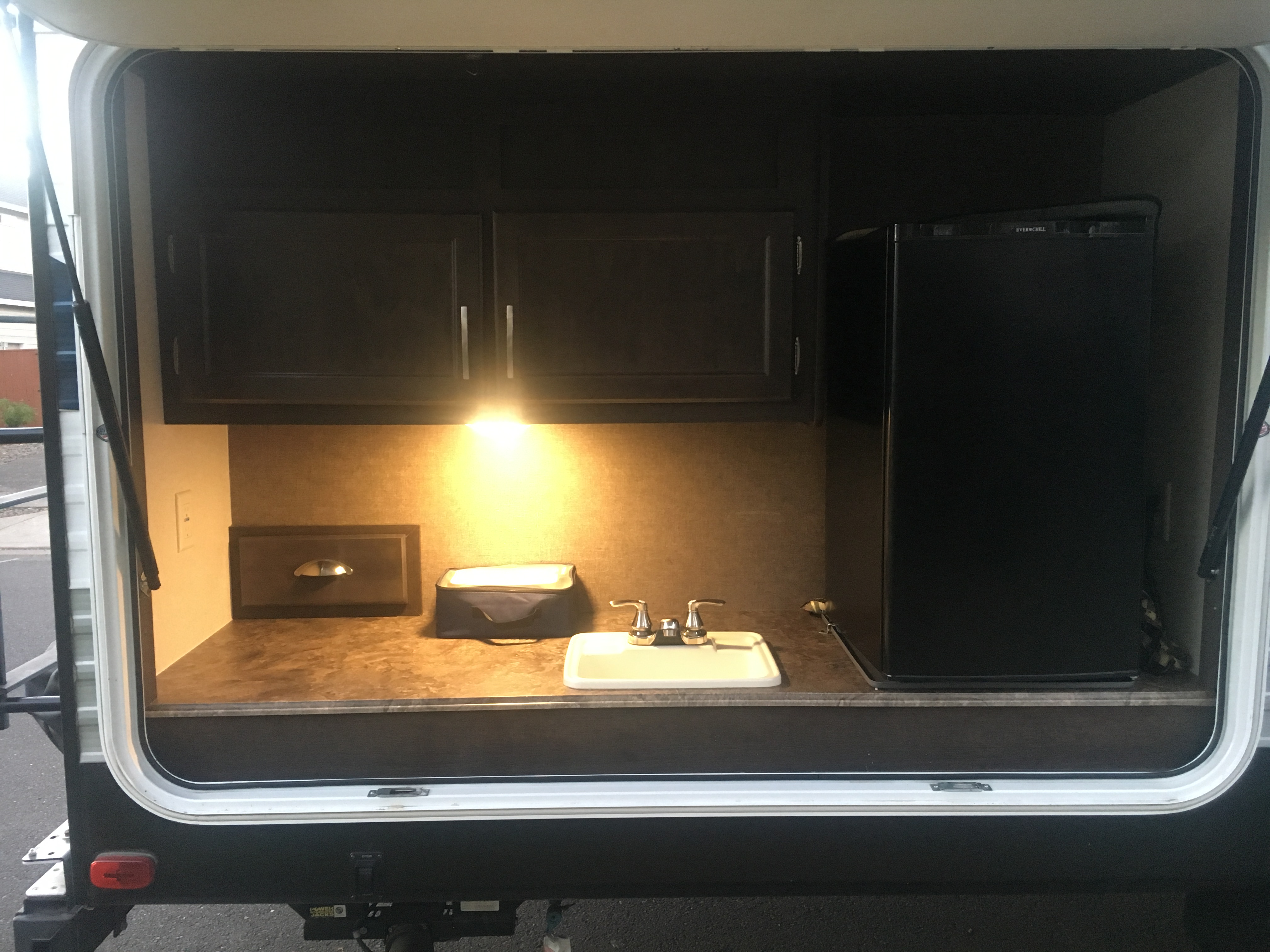 Outside refrigerator and sink? Yes please! I rarely cook inside having a mini kitchen outside makes it super simple to cook for the entire family. Not to mention that there's a small bbq that swings right around from the back of the trailer.. Forest River Evo 2016