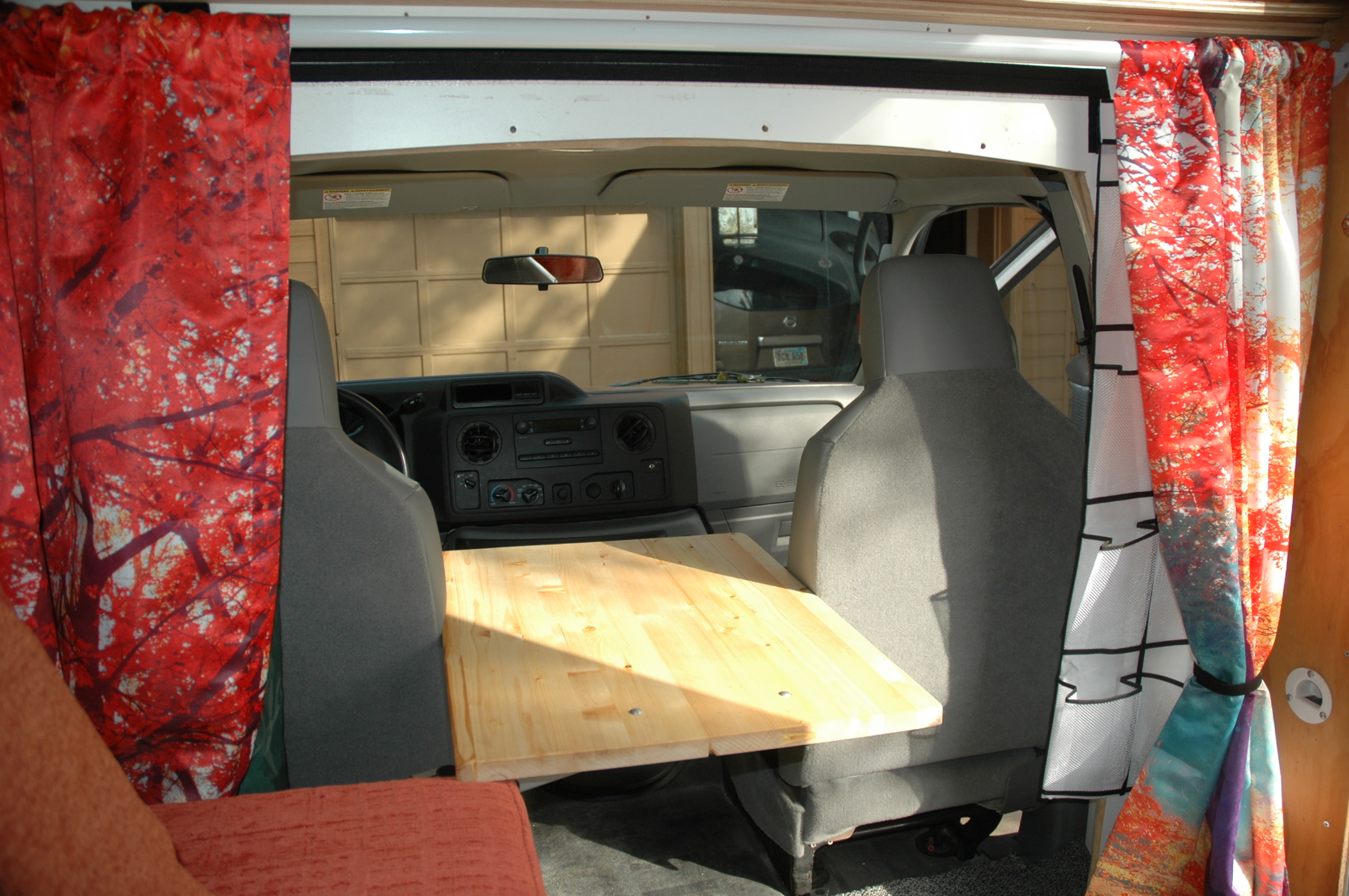 Colorful cab curtains can be pulled back and the table rotated during travel.. Ford E350 Box Van 2012
