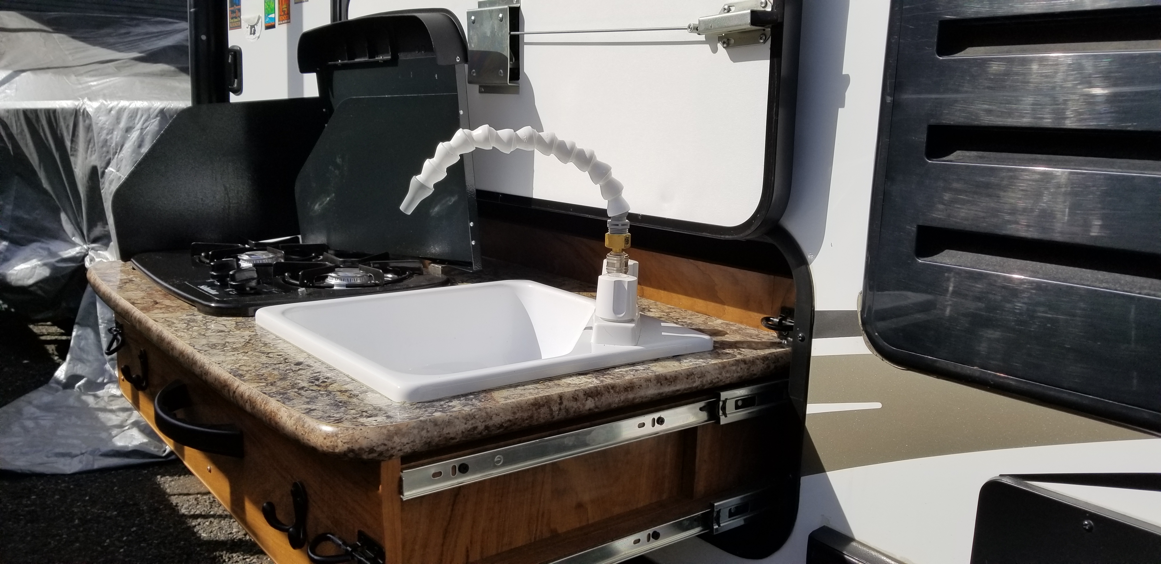 Slide-out outdoor kitchen.  2 burner stove and sink. Outdoors Rv Manufacturing Creek Side 2016