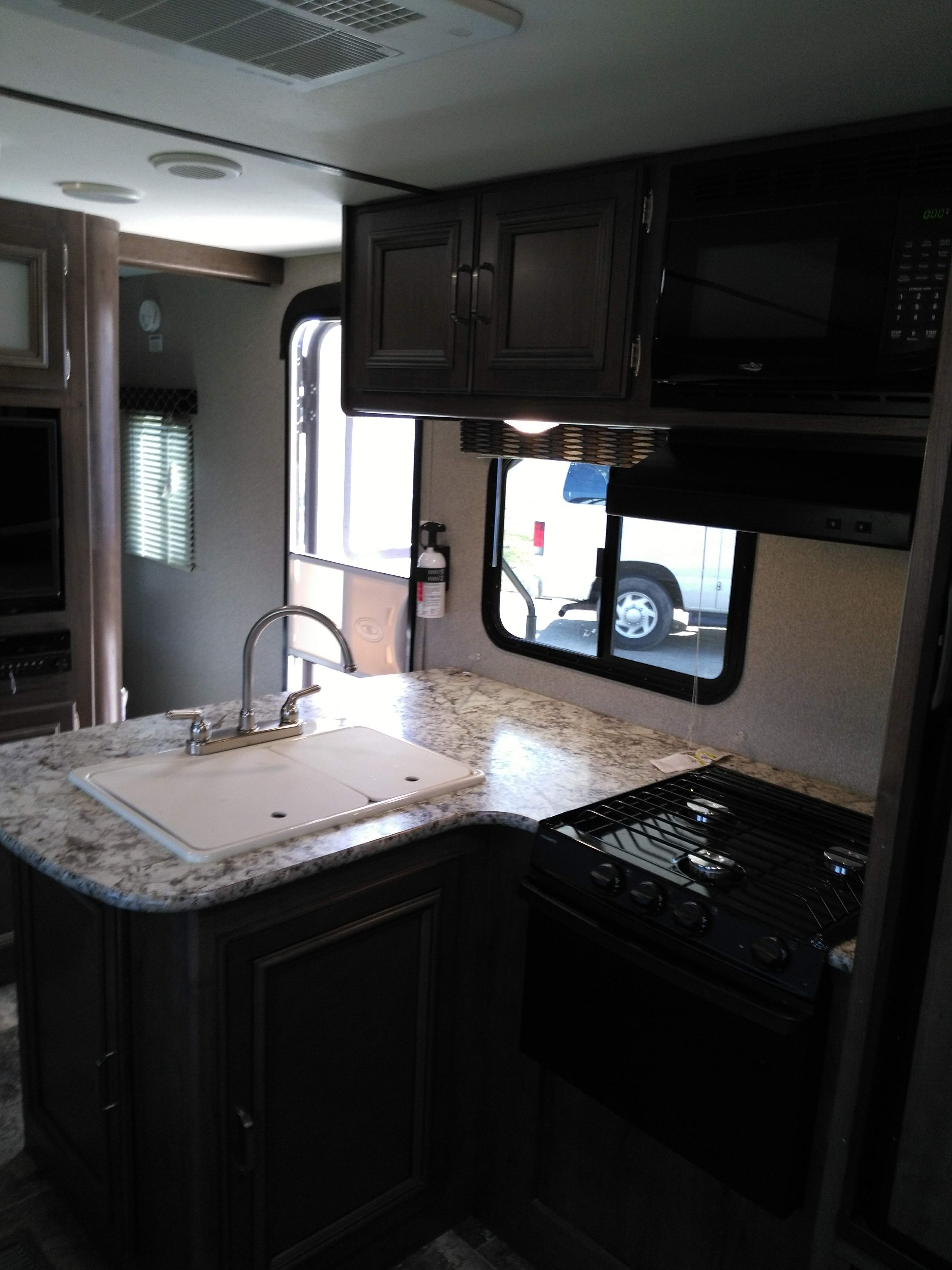 Double sink.  Gas stove, oven, and microwave.  Toaster oven and coffee maker included.  Refrigerator with freezer.. Keystone Passport 2018
