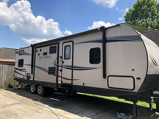 Outside of RV with slide ins pulled in . Palomino Solaire Ultra Lite 2013