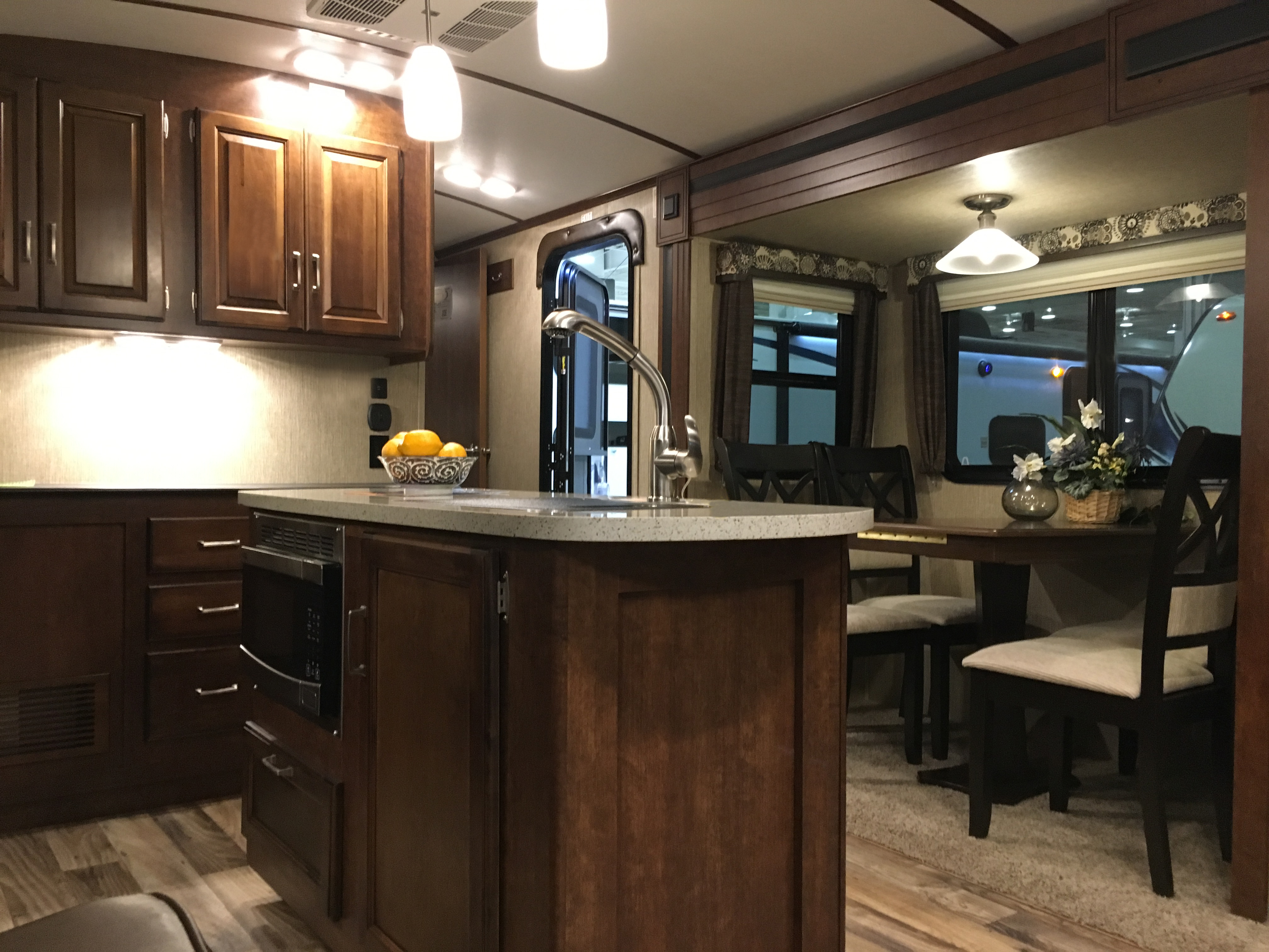 Spacious, fully functional kitchen and dining area featuring a corian countertop with large, deep sink and a microwave. Dining seating for 4 with large picturesque windows.. Keystone Outback 2017
