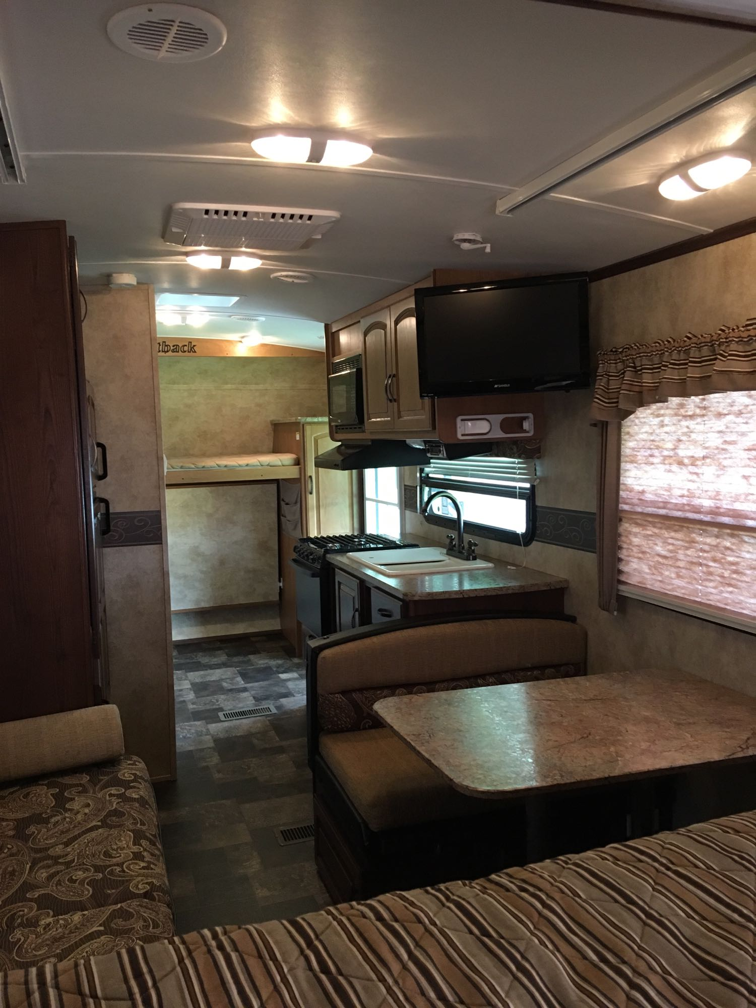 Indoor kitchen and rear bunks. Lower bunk can be folded up for extra storage space while traveling.. Keystone Outback 2013