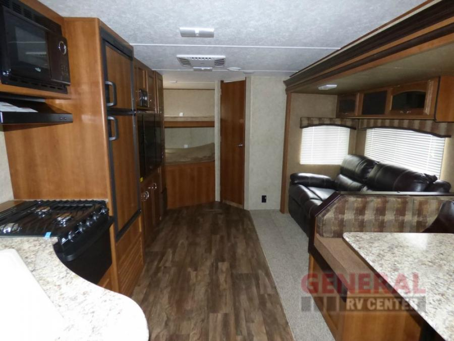 Inside of Camper - facing bunk beds to left and bathroom door. Also couch on right unfolds to full queen bed. . AVENGER 27DBS-P 2017