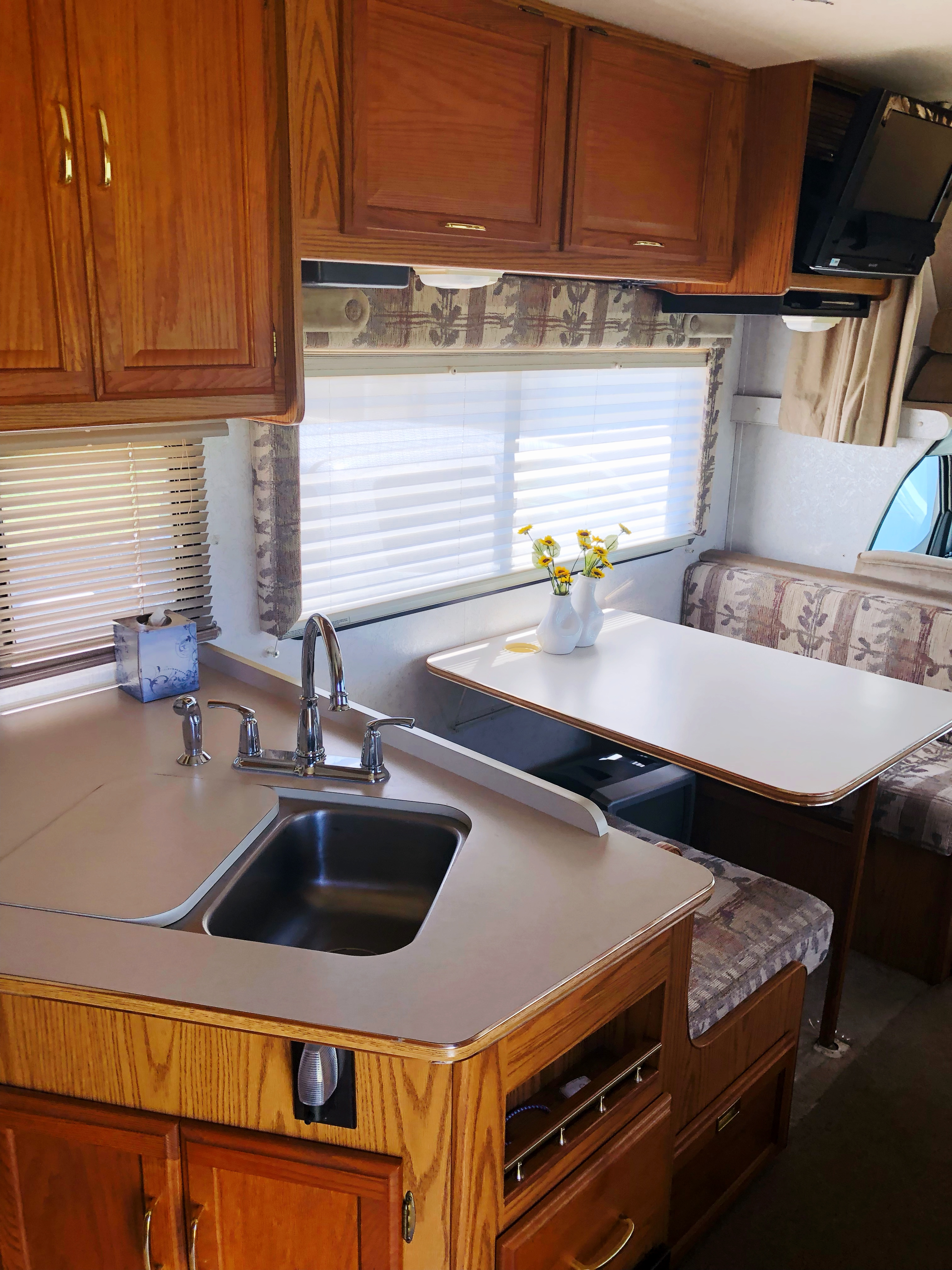 Double sided stainless steal sink with a cutting board. Dinette makes into a bed for two children or one adult.  Faucet set is new. . Itasca Spirit 2000
