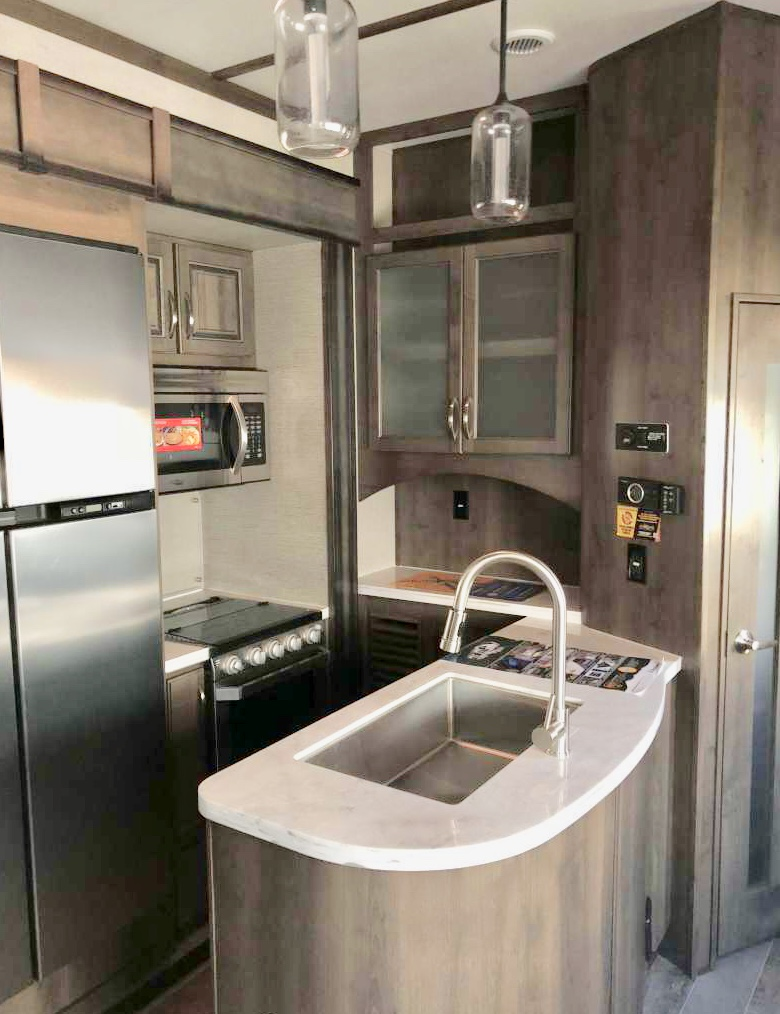 This is the kitchen area. The fridge opens as french doors,  and is the size of ur basic home fridge. Comes with a convention/microwave in one. The stove, has a descent size oven for the baker's. I have stored all kinds of cleaning supplies under the sink for ur use.. Dutchmen Voltage 2019