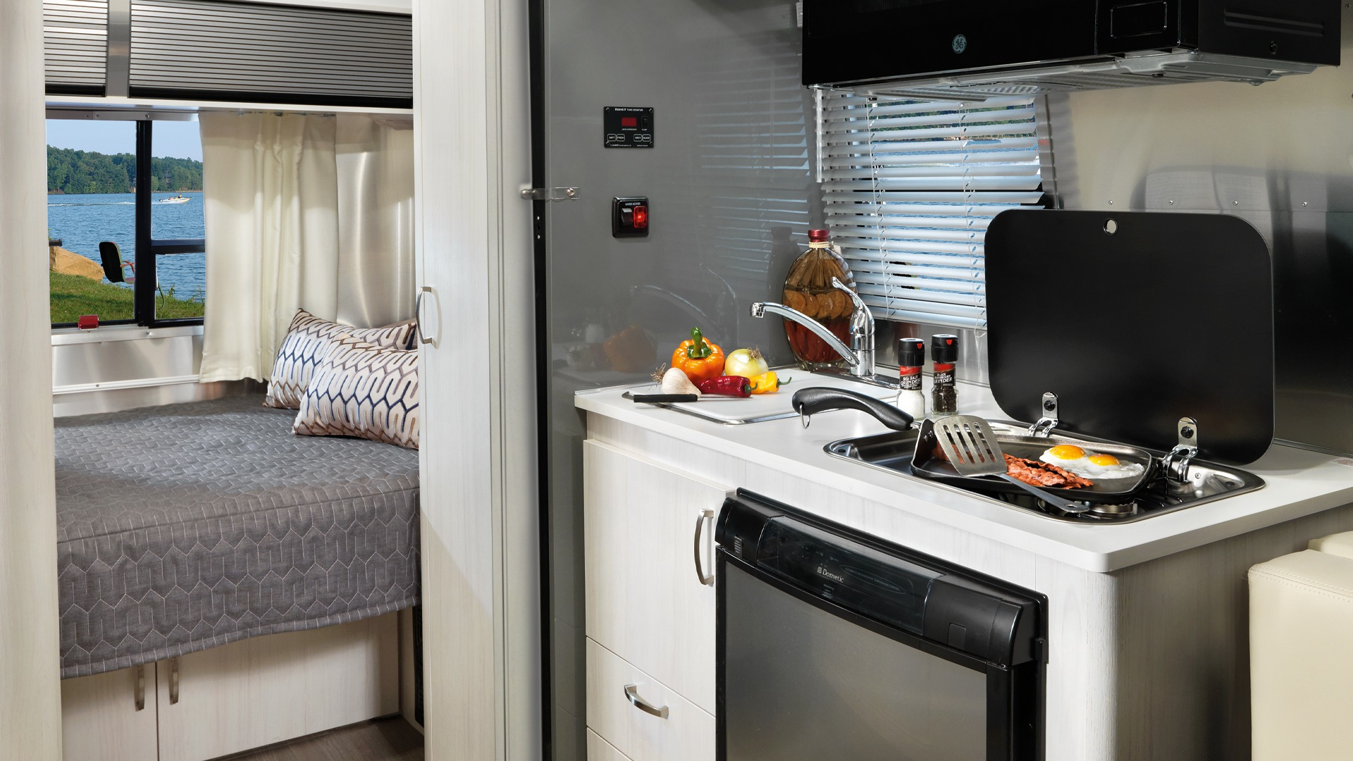 Kitchen is equipped with a two burner stove, refrigerator, sink and microwave. Airstream Sport 2019