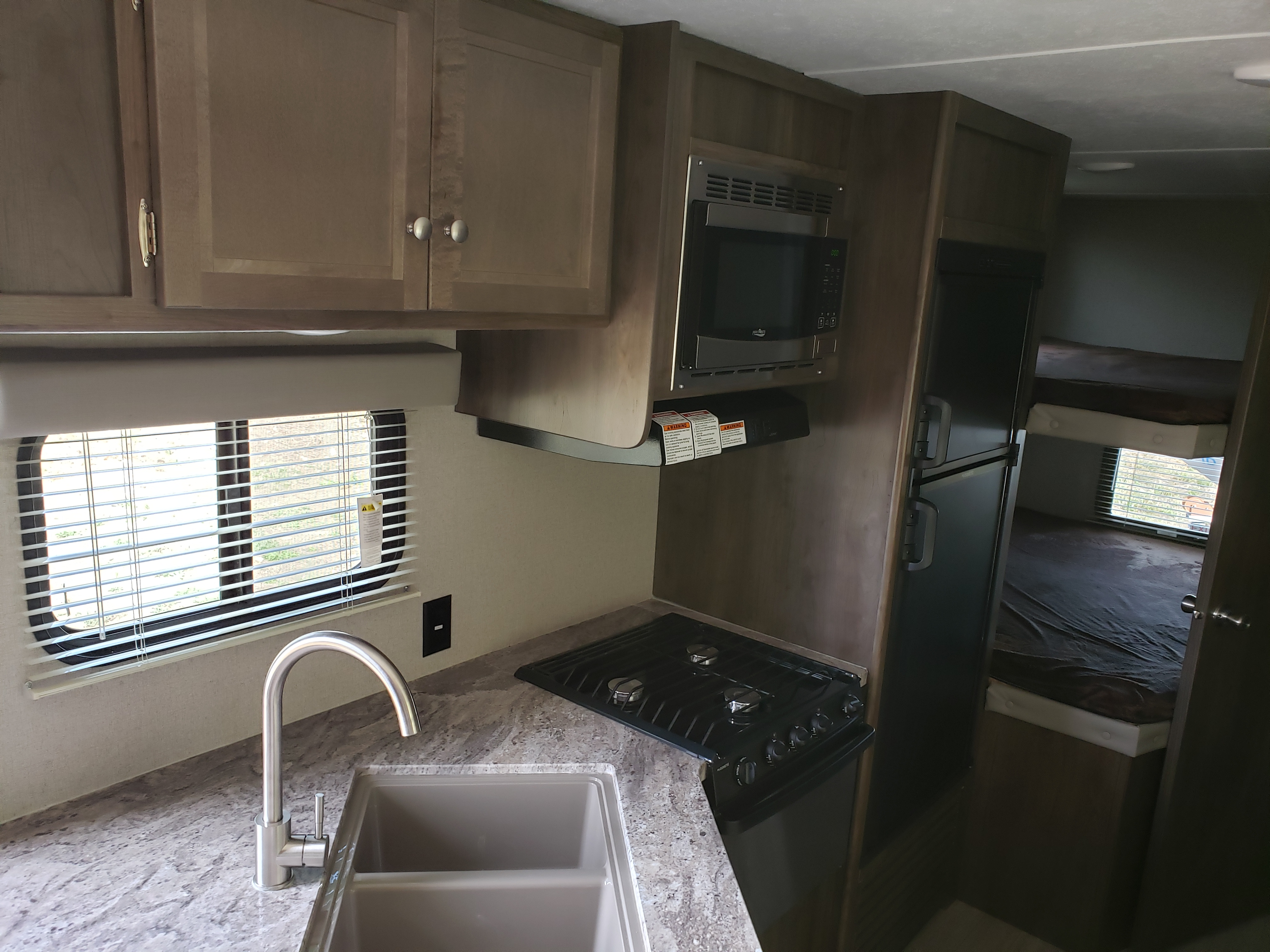 Rv has a nice kitchen with a sink, stove, range, microwave and fridge inside.. Coleman Lantern 2019
