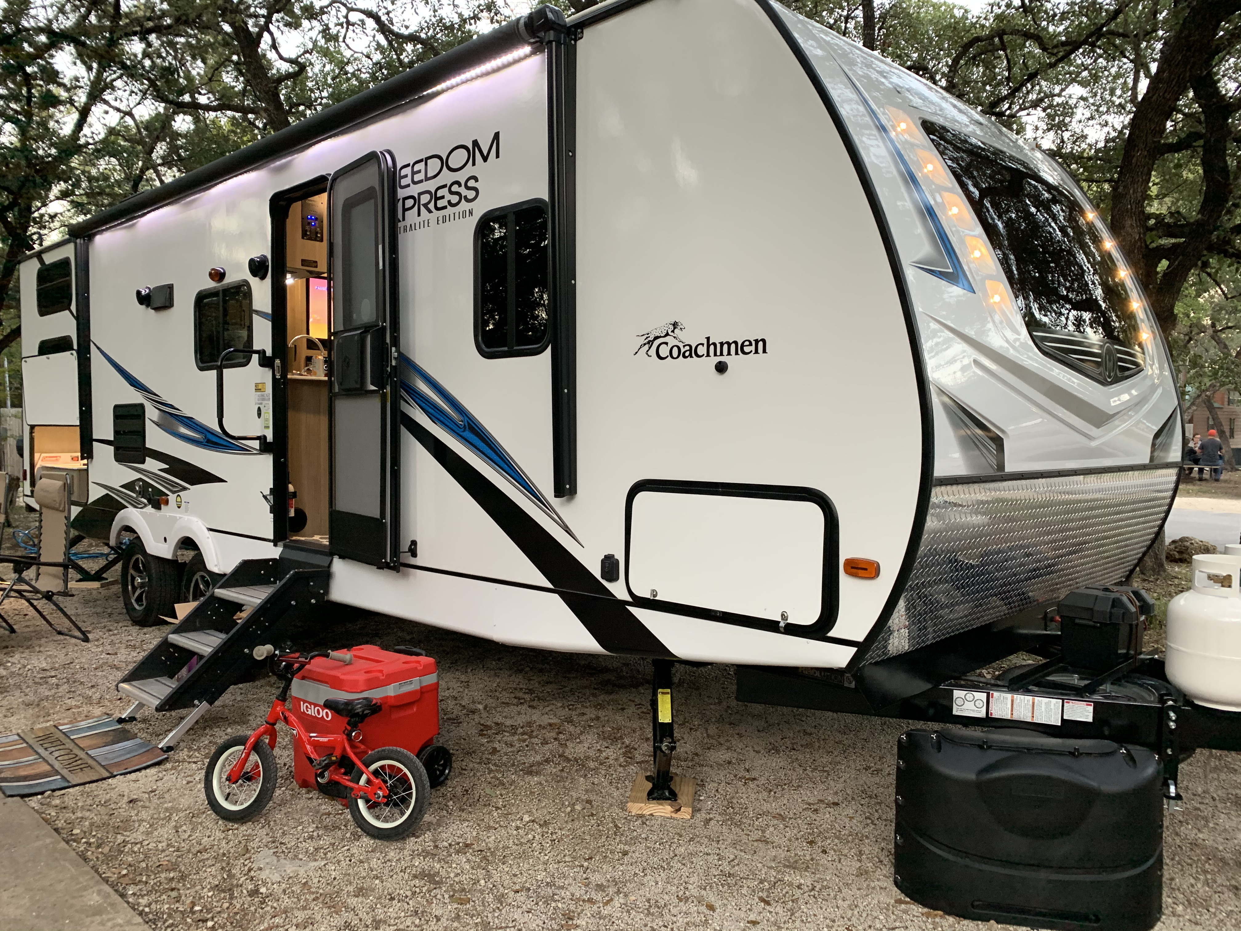 Built in exterior lighting under the awning and in front of the trailer add plenty of light at night . Coachmen Freedom Express 2020