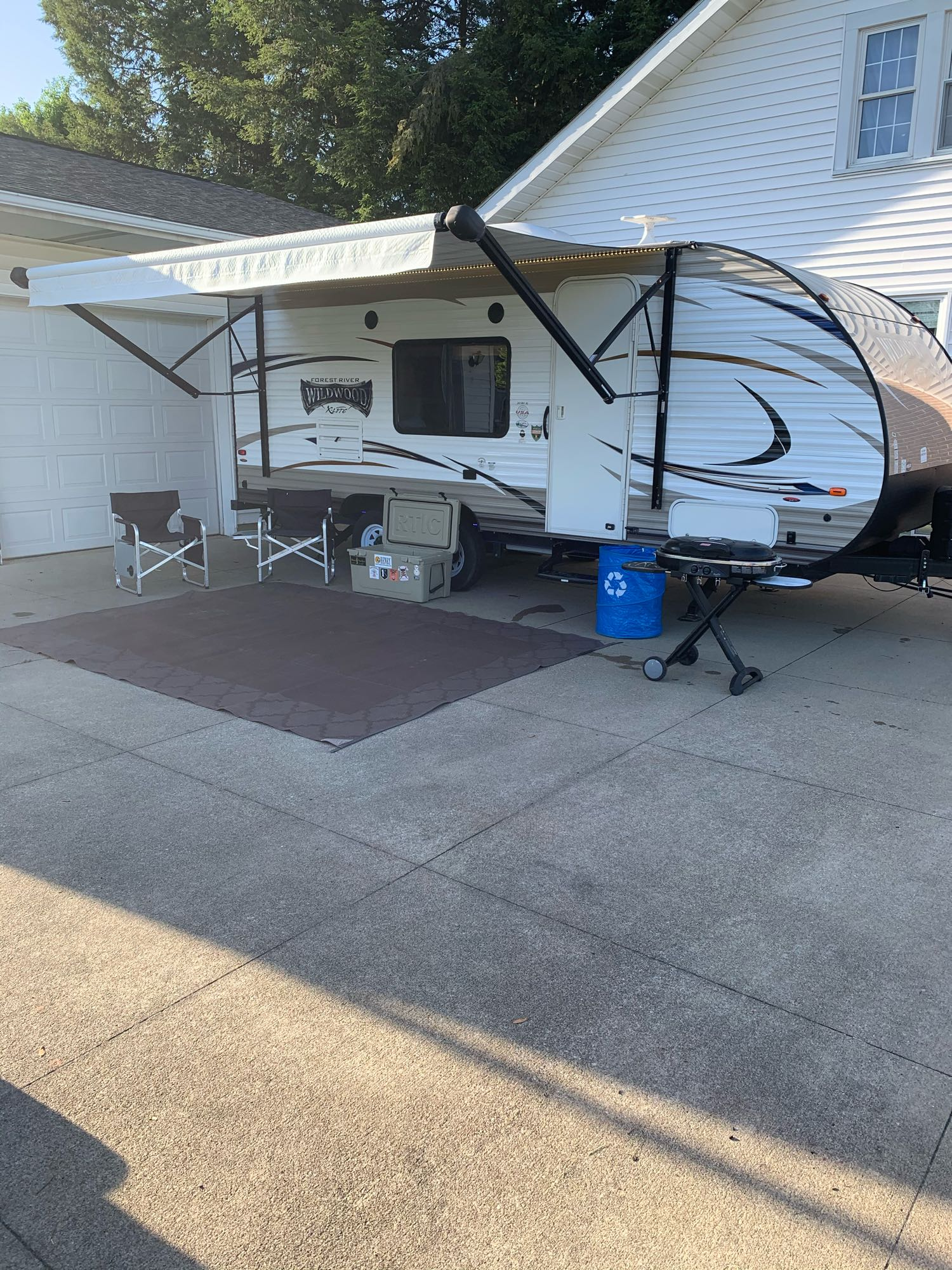 Rental includes 4 camping chairs (only two shown). Trash/recycling container for easy disposal of trash. Coleman road trip grill (propane adapter included). Camping all weather rug. RTIC 65 cooler. Picture shows LED under coach lights and under awning LED strip as well.. Forest River Wildwood X-Lite (201BHXL) 2018