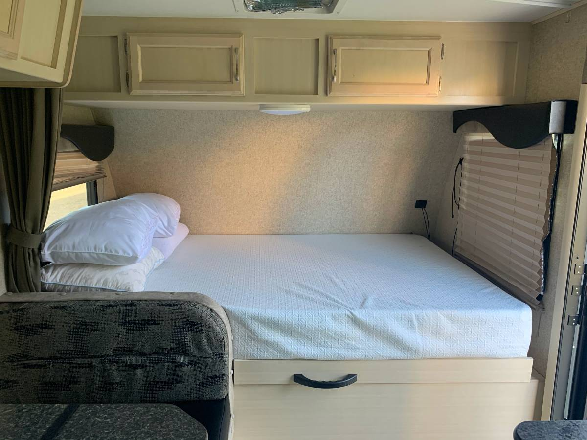 Large queen bed with a memory foam mattress. This bed also lifts up to reveal a huge storage compartment underneath.. Winnebago Micro Minnie 2018