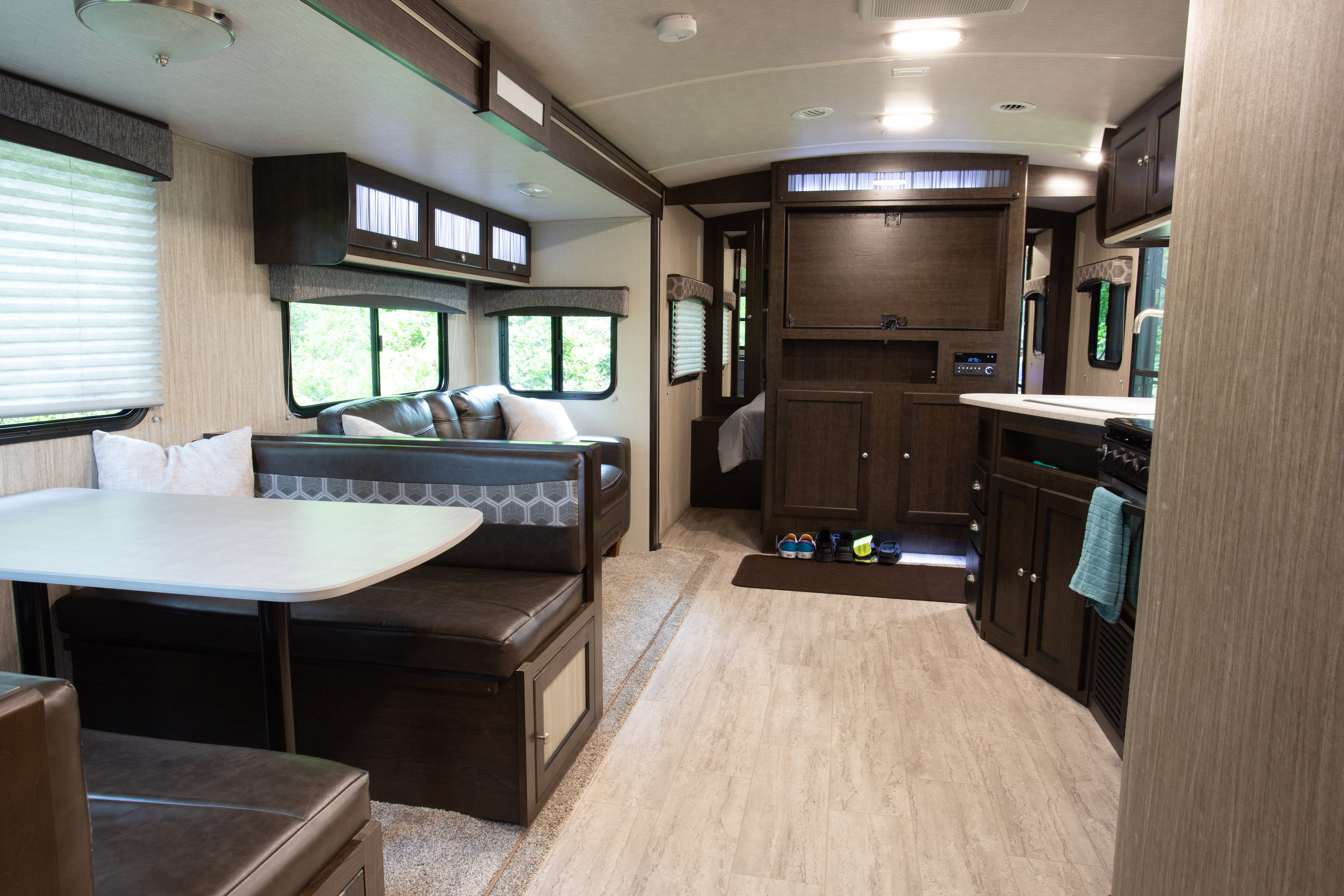 Spacious living space with a booth style dining area and couch in the large slide out.. CruiserRvCorp ShadowCruiser 2020