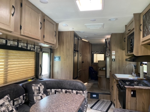 Full kitchen with table, stove, microwave, sink, oven, fridge. Coachmen Freelander 2017