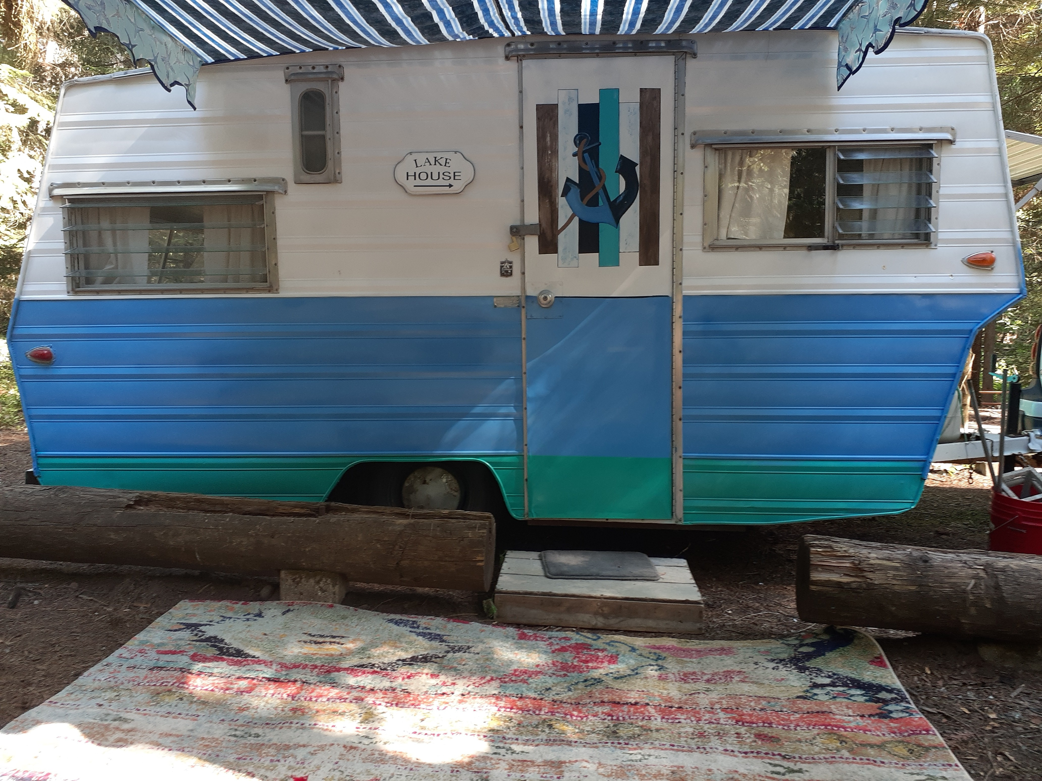 A rug, awning, and two camp chairs are provided.. Aristocrat Lo-Liner 1965