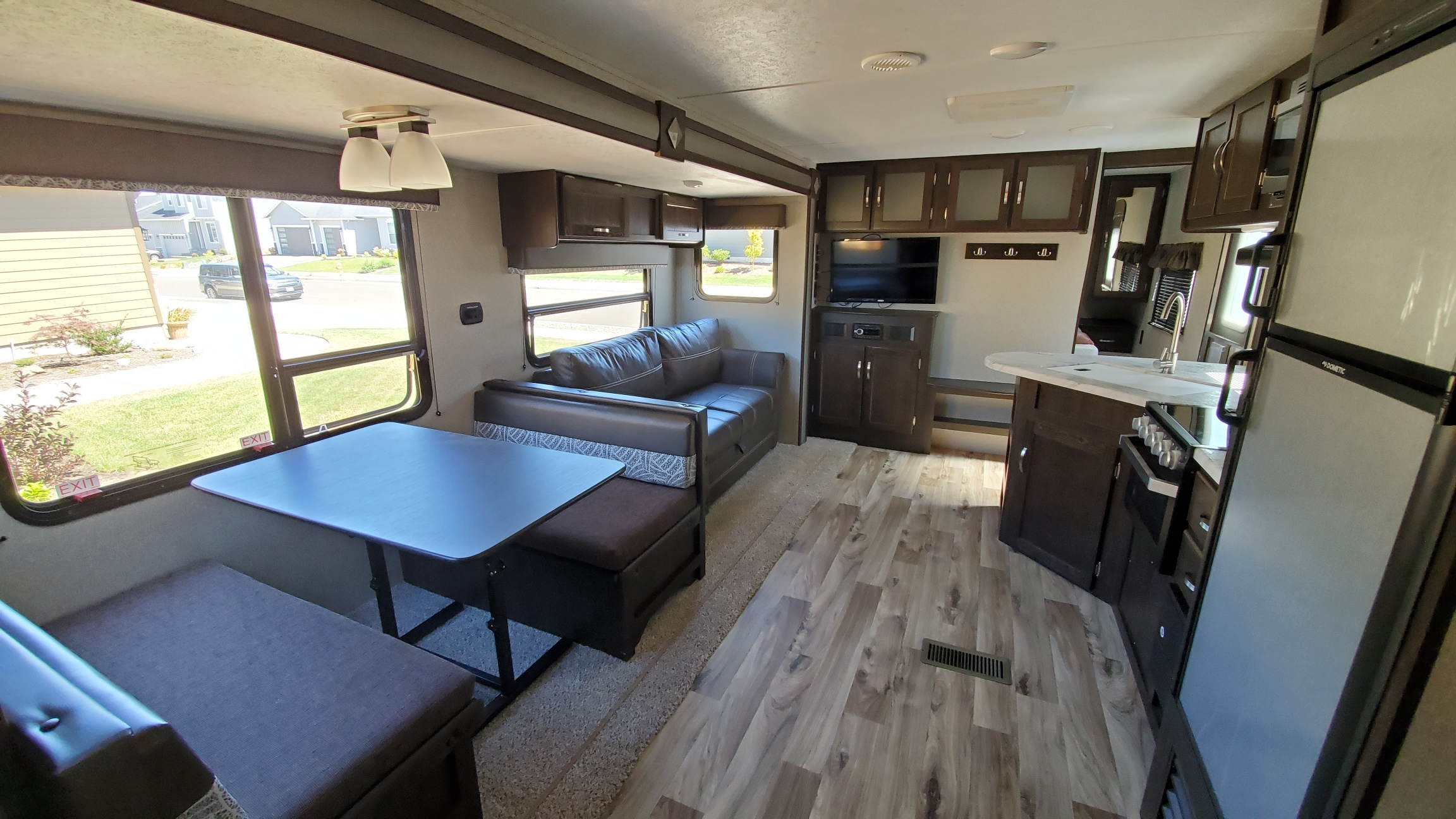 Dinning table and couch with entertainment center. Keystone Springdale 2019