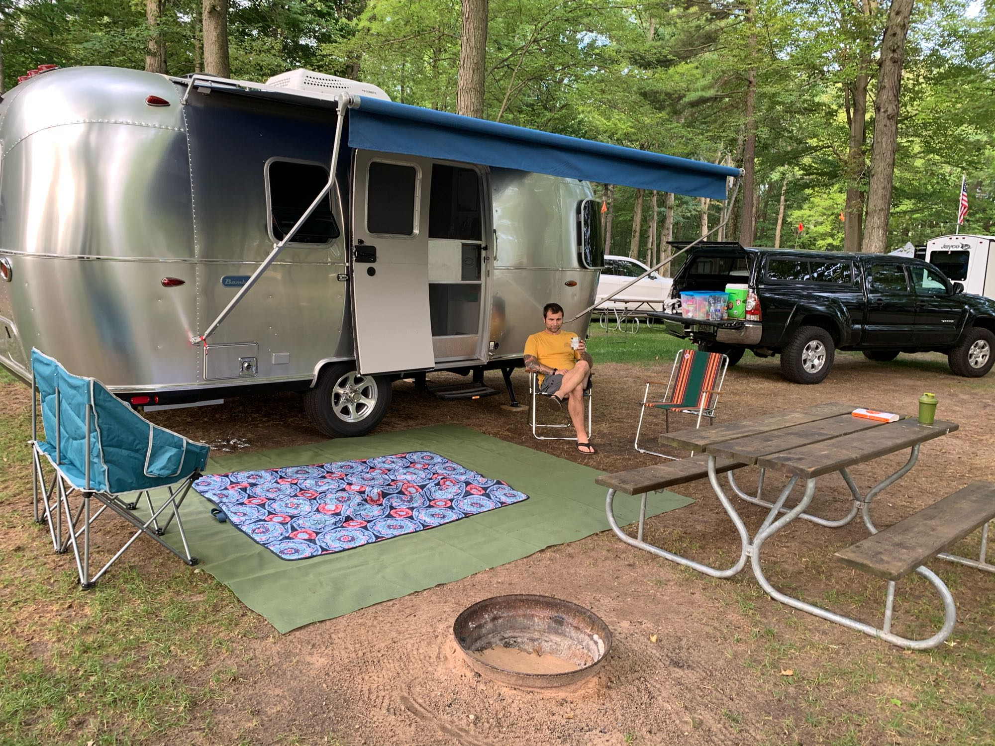 Modest set up for kids to play under the awning on the floor mat and a blanket.. Airstream Bambi 2020