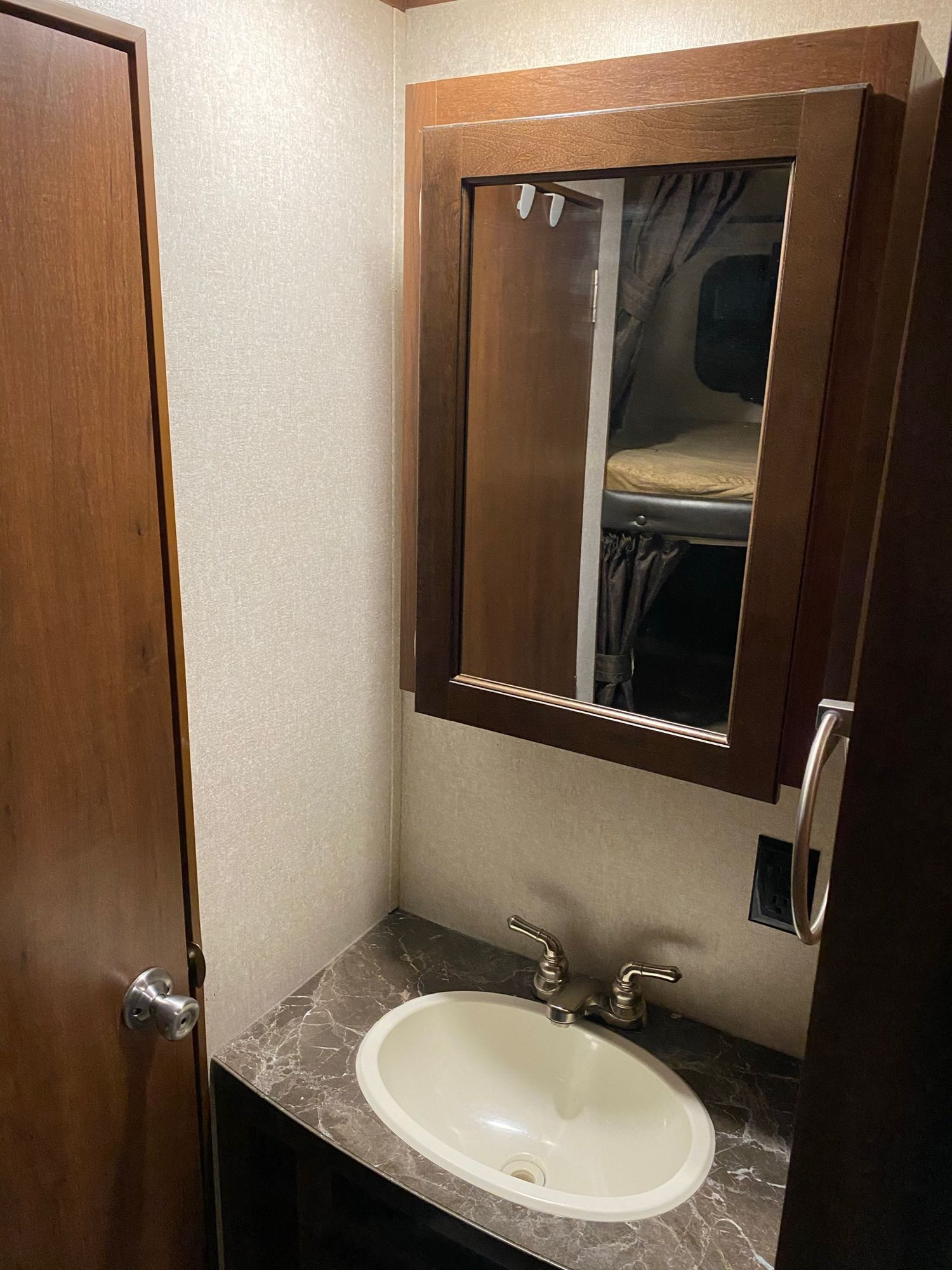 The bathroom sink features a mirrored vanity with storage behind and below.. Jayco Flight 2017