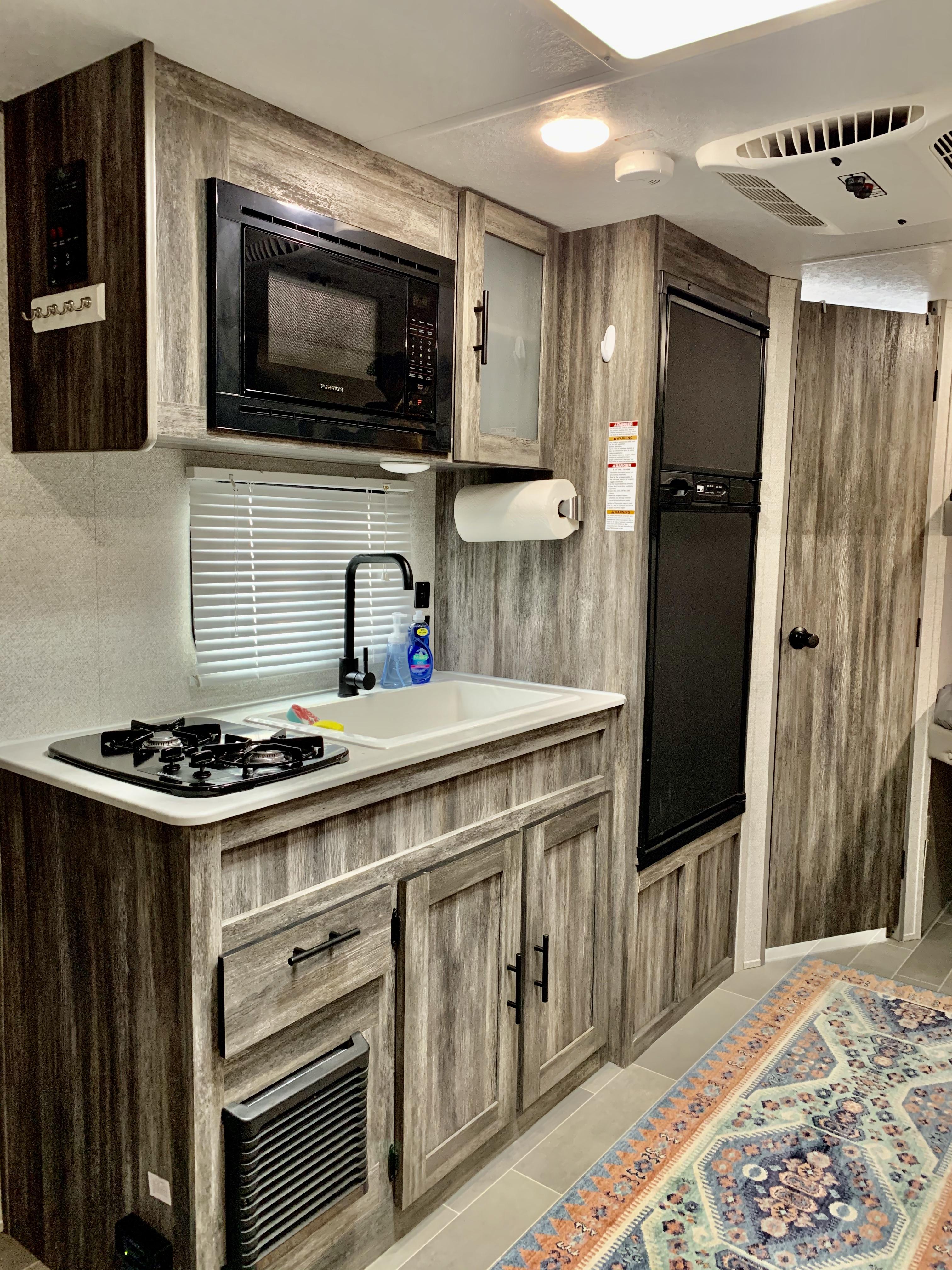 Modern kitchen, sink, refrigerator,2 burner stove, microwave. Forest River Salem 2020