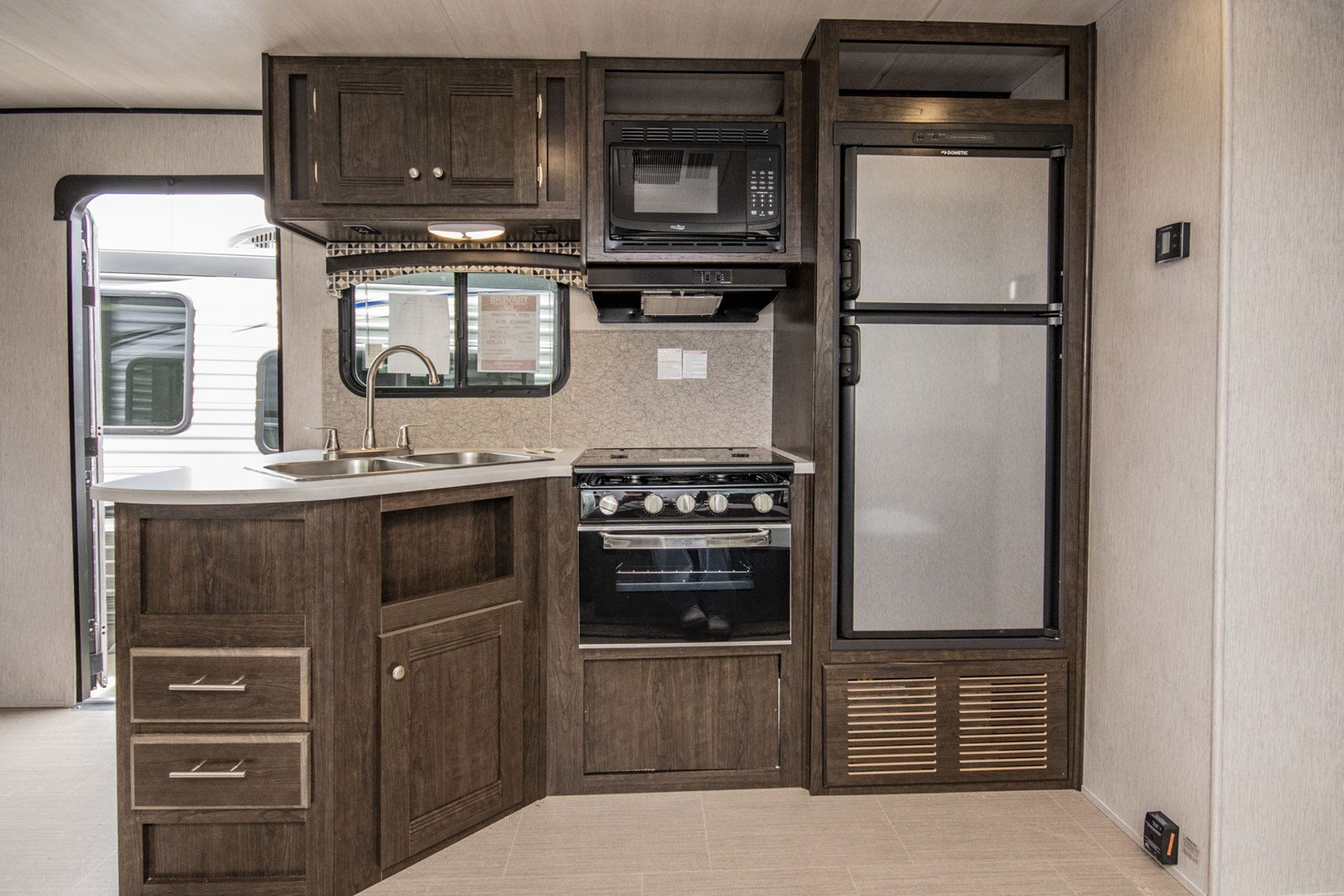 Kitchen is furnished with plasticware and cleaning supplies.. Heartland Prowler Lynx 2019