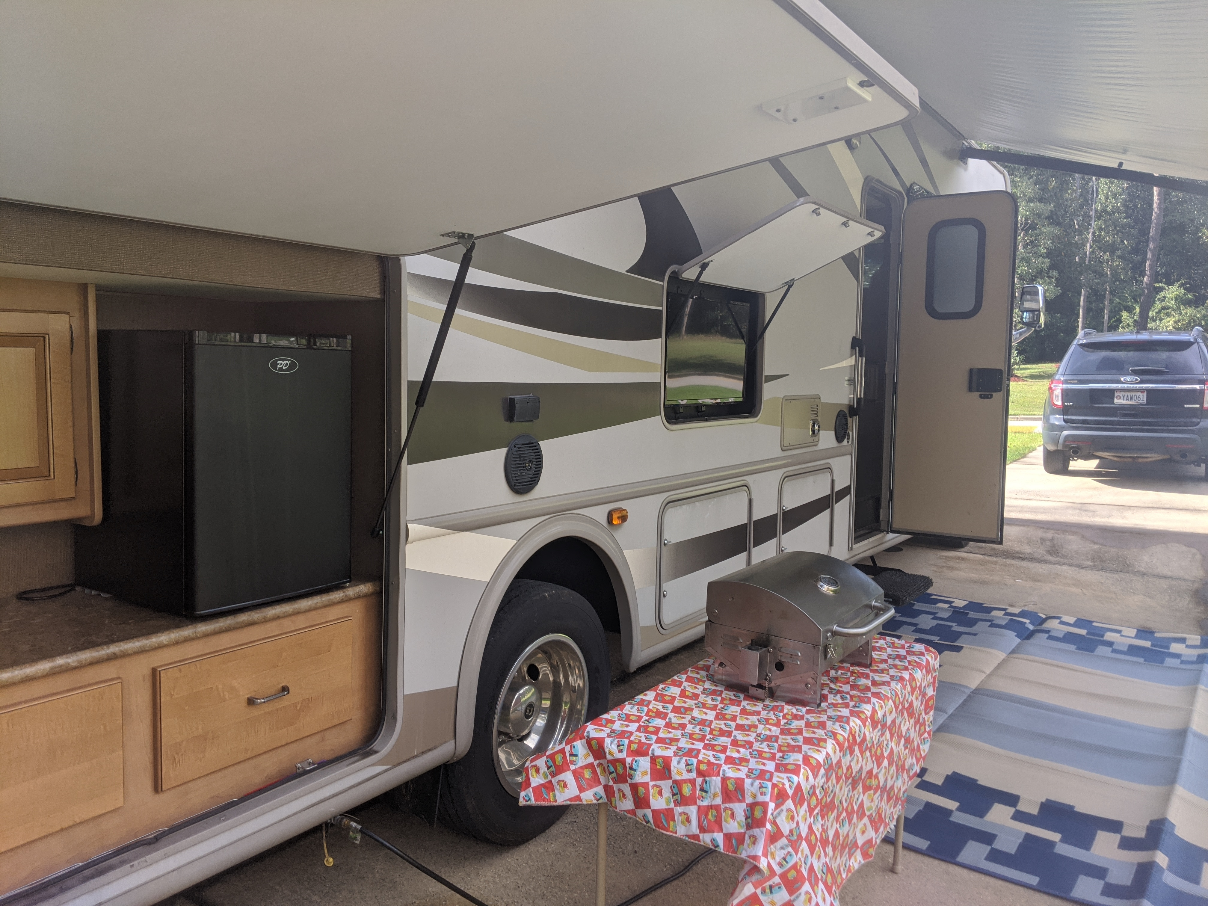 Outside sink, fridge, television, and grill.. Thor Motor Coach Hurricane 2016