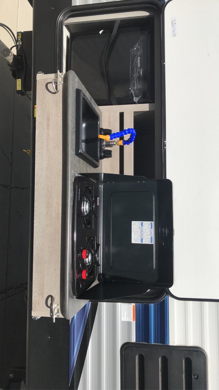 Outside kitchen with 2 burner stove, sink, and mini fridge. Springdale 240BHWE 2021